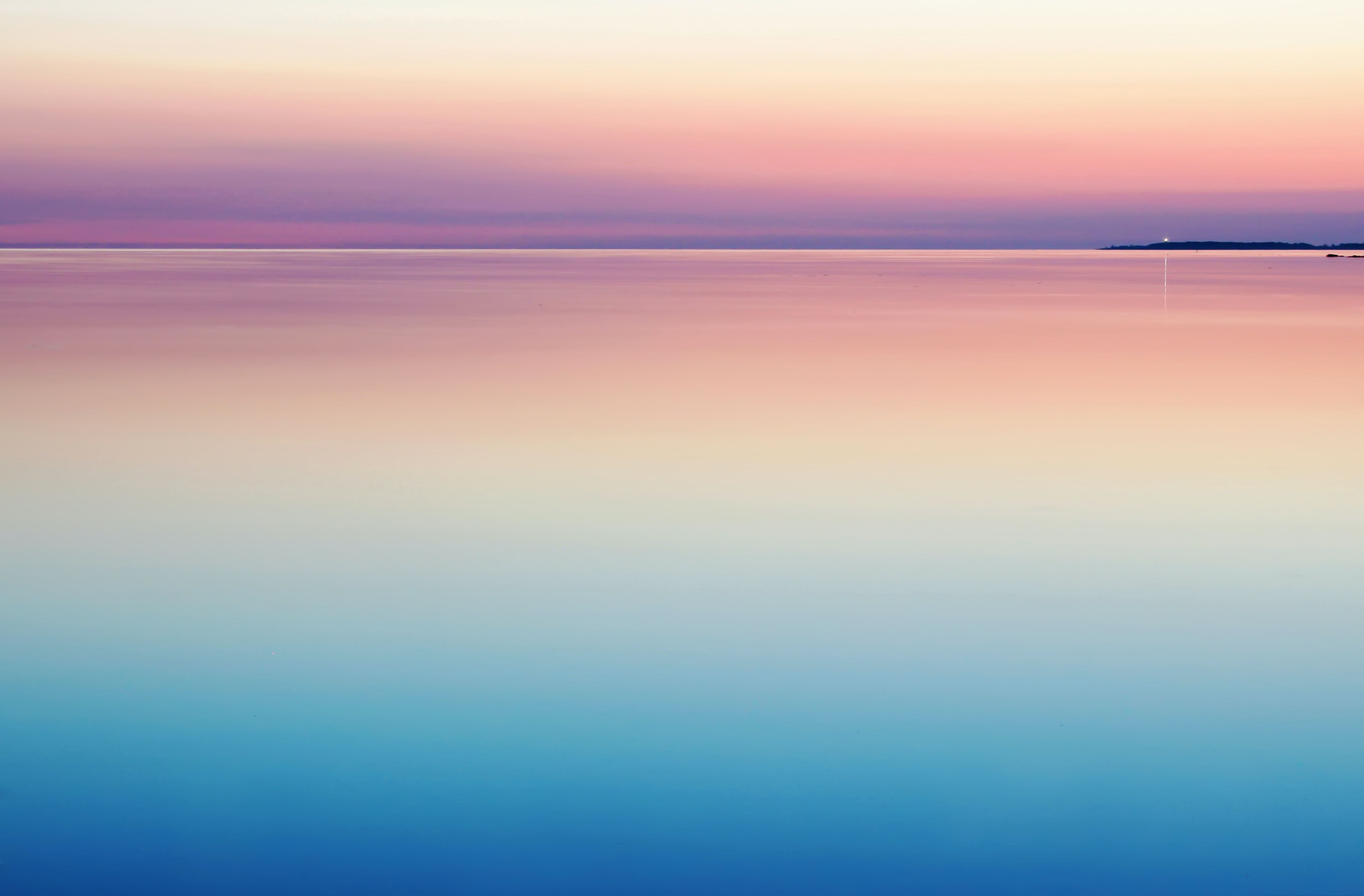 A peaceful and serene pastel pink and purple sunset reflecting on still and calm water