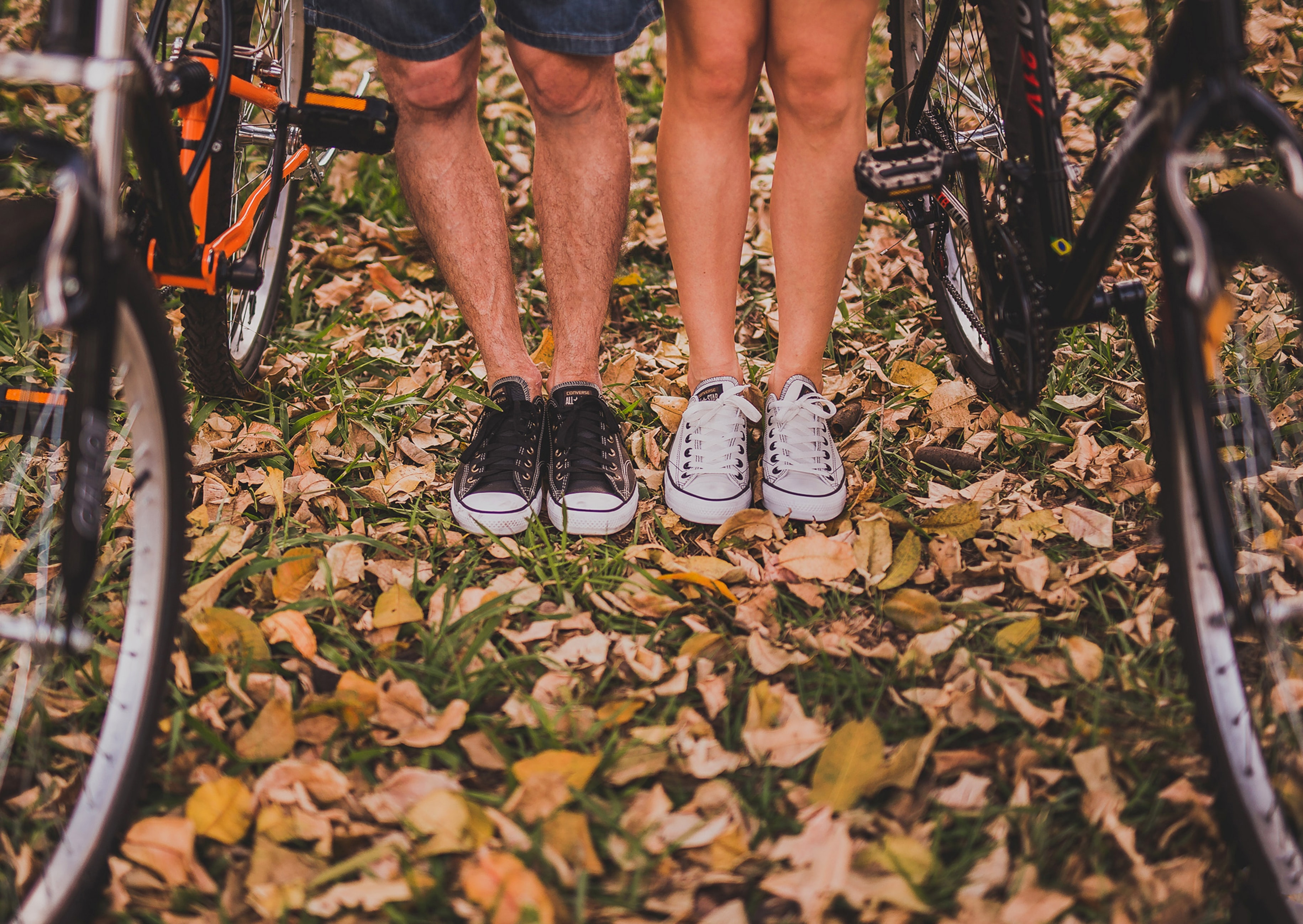 Close-up of man and woman's feet and knees together while pausing from a bike ride