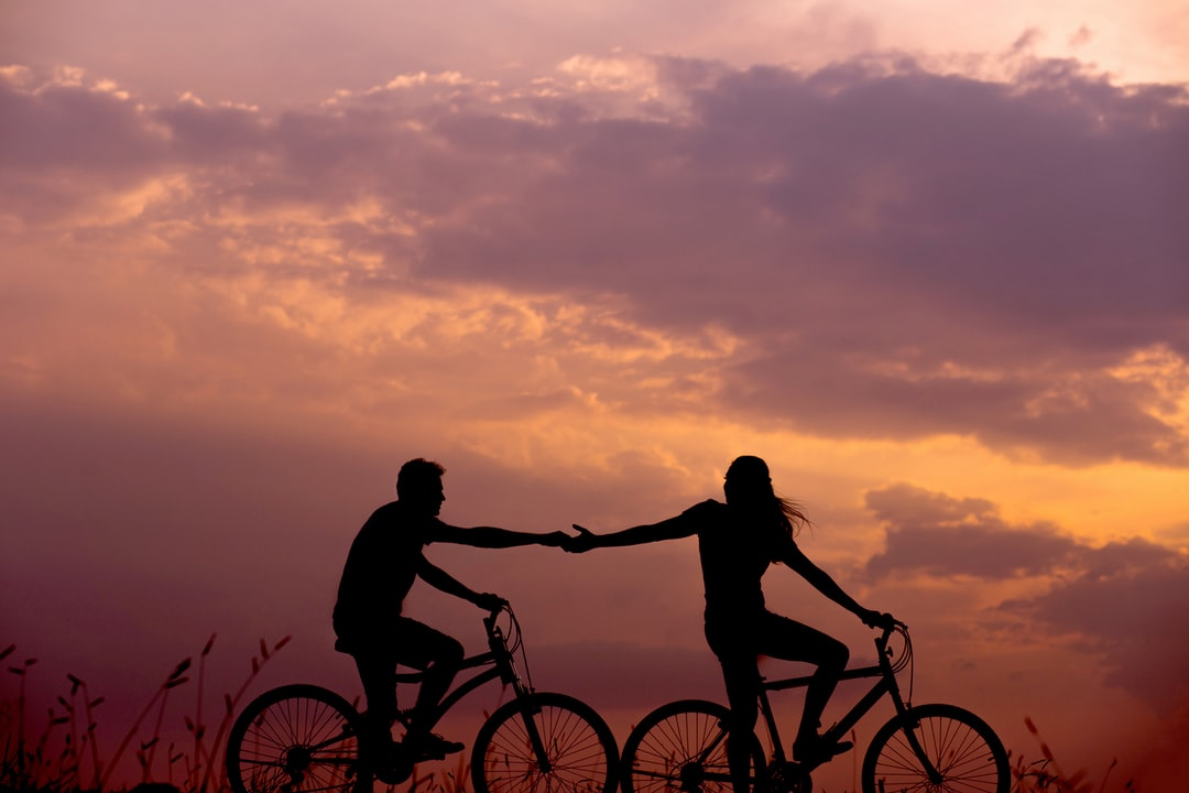 Lovers share a silhouetted bicycle ride, hands reaching out to each other