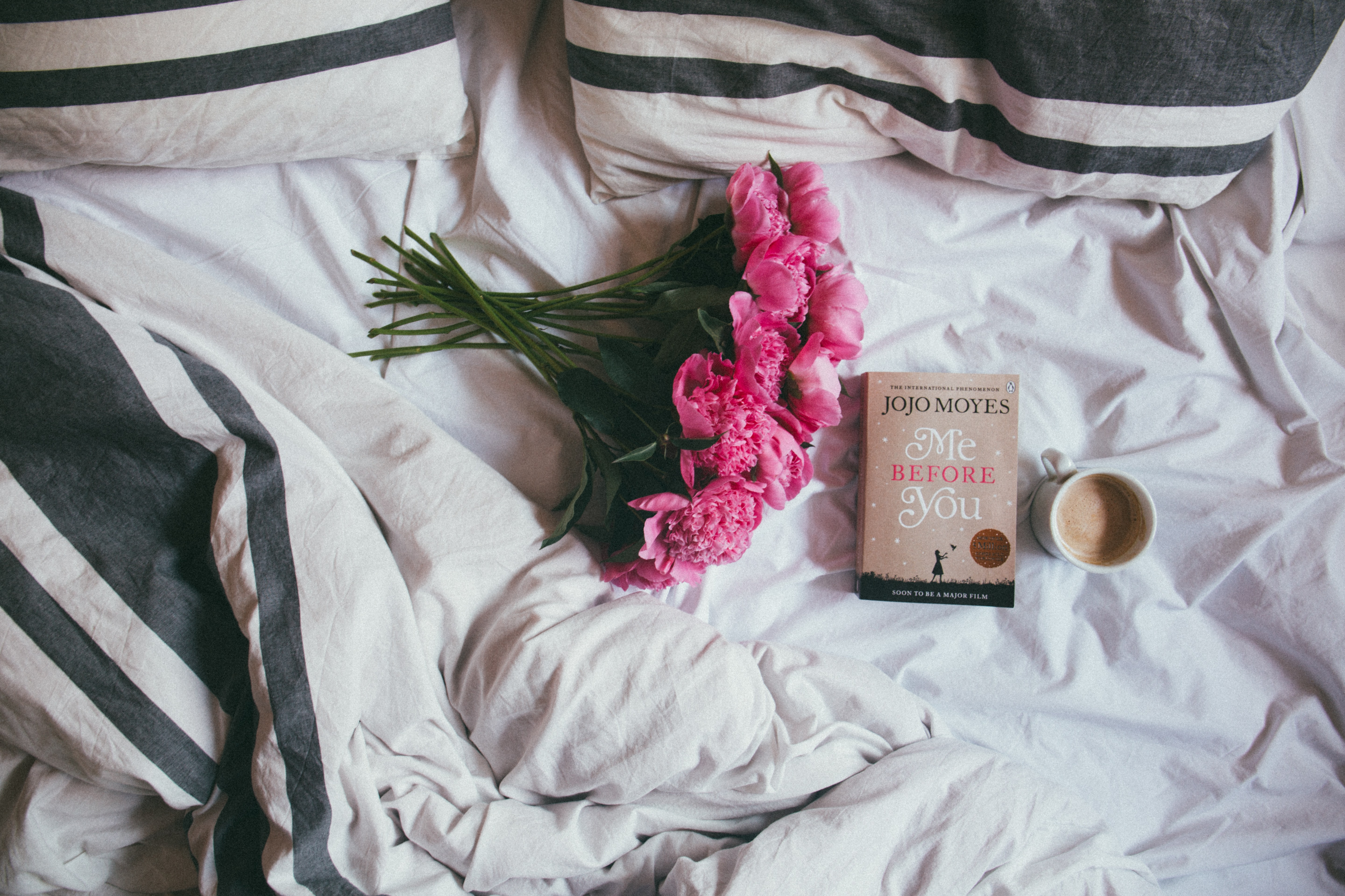 bouquet of pink flowers on top of bed