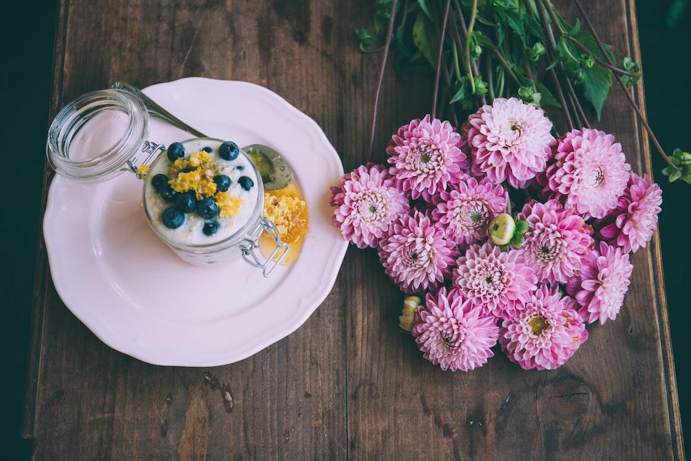pink dahlia flowers beside ceramic plate with jar