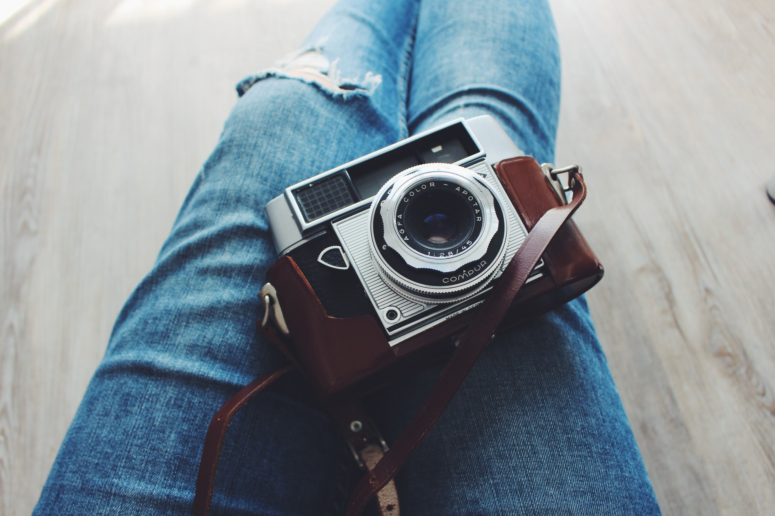 A vintage film camera on a woman's lap.