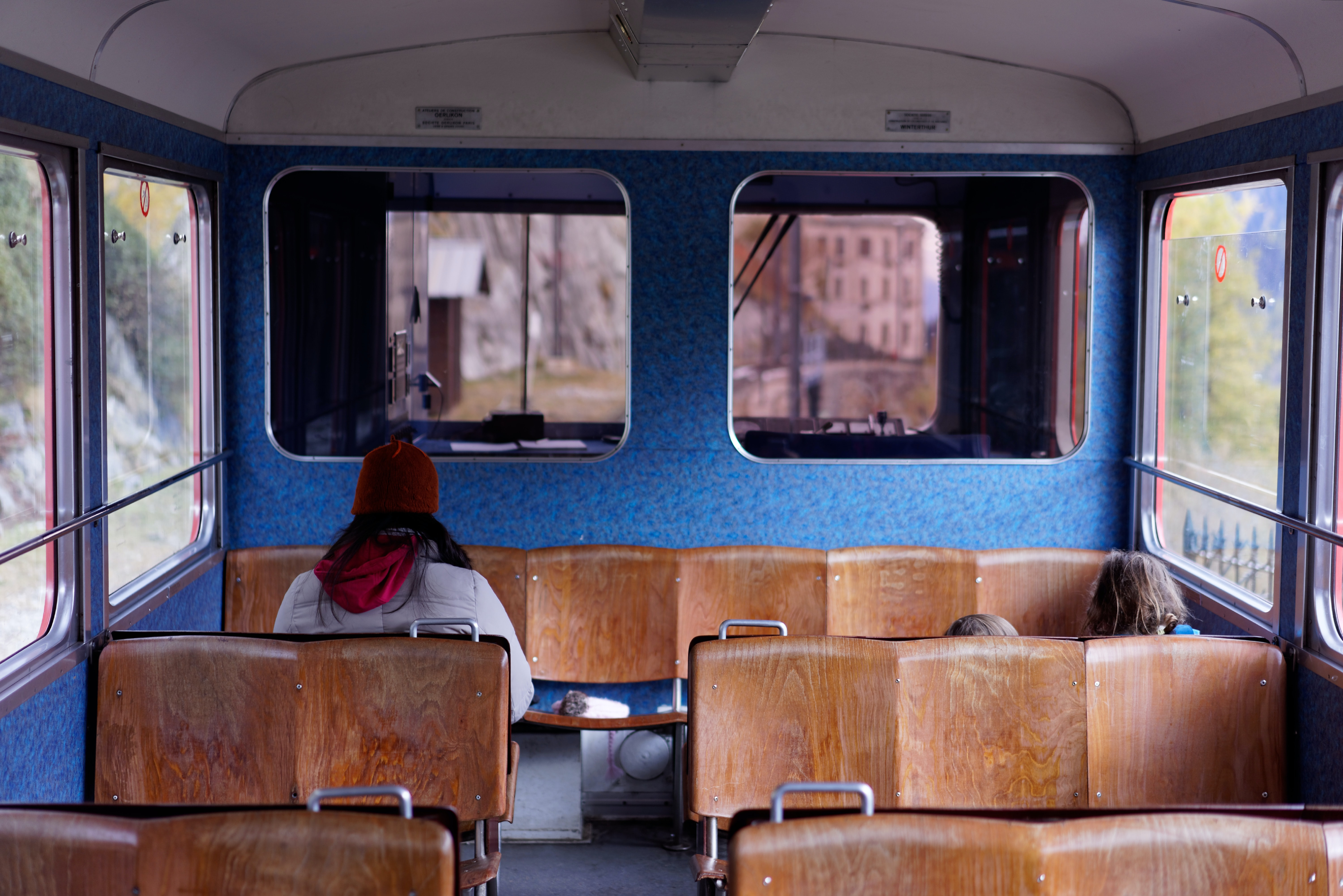 The inside of a train with wooden seats