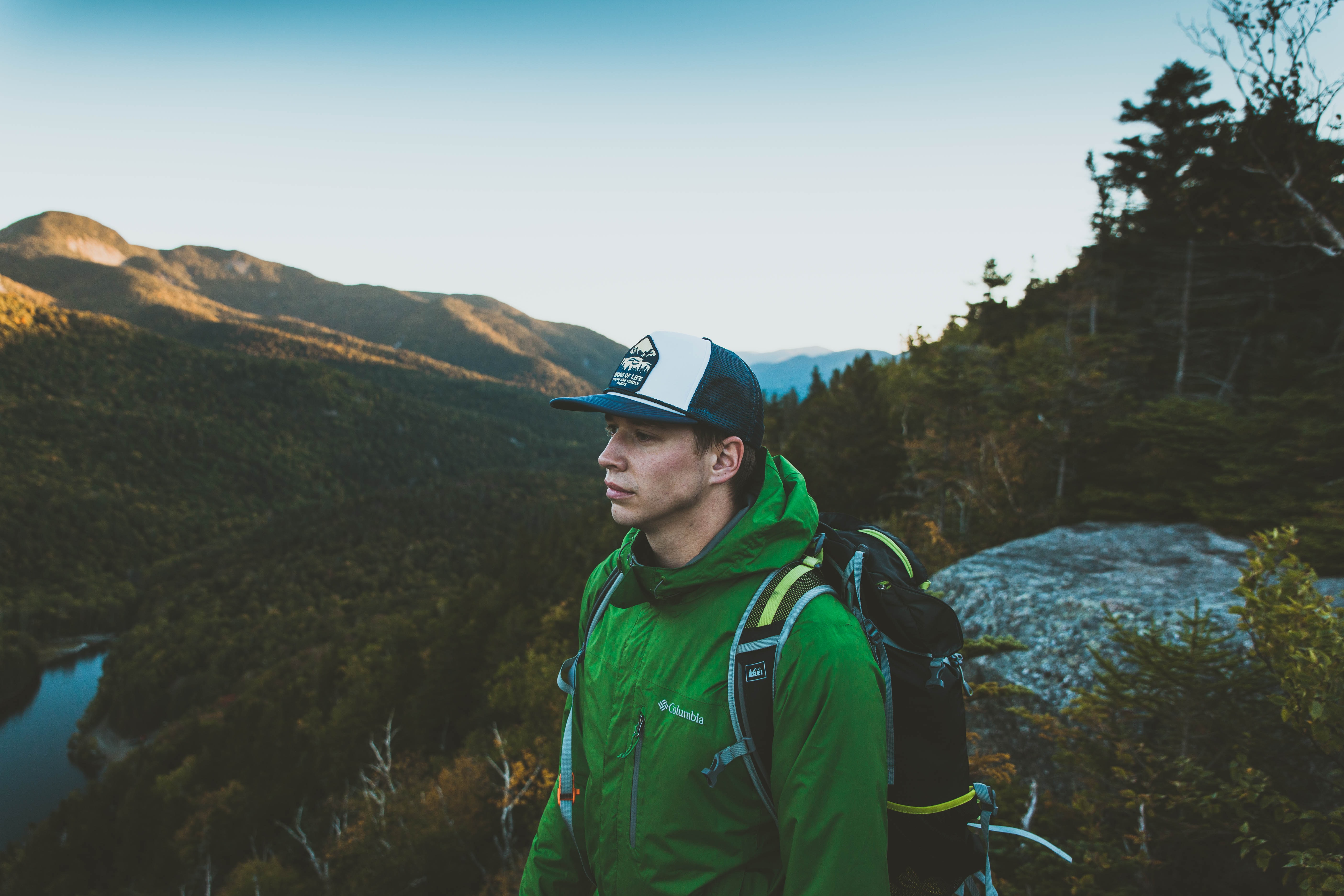 A young male hiker in a wooded mountainous landscape