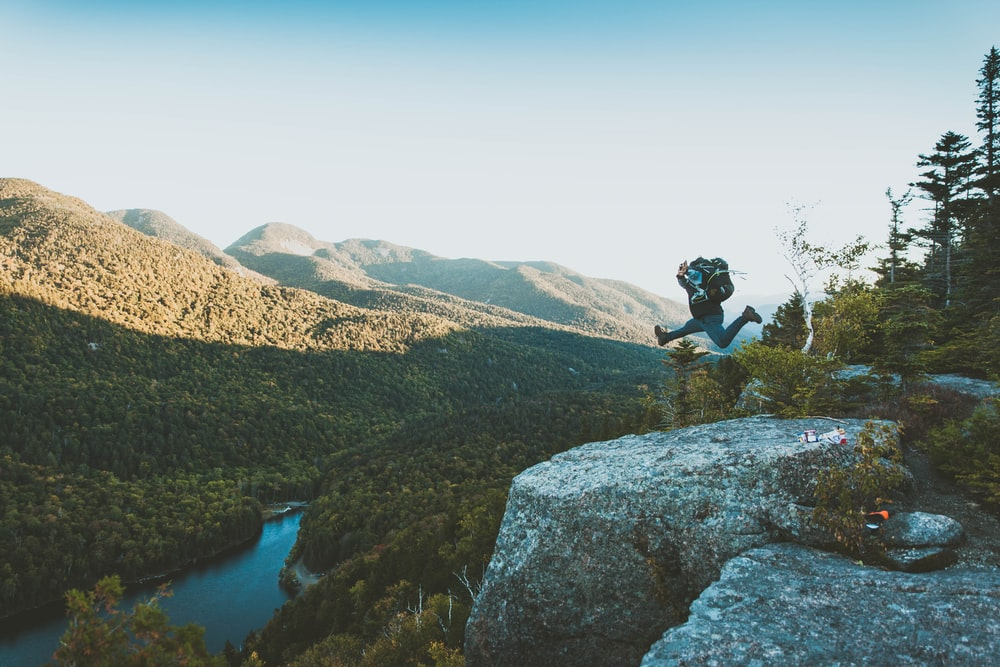 time lapse photo of person jumping from cliff within mountain range