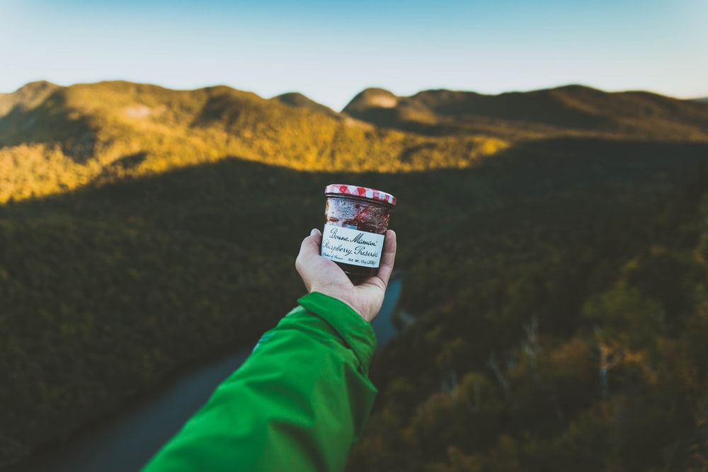 person holding clear glass jar with cap near mountain