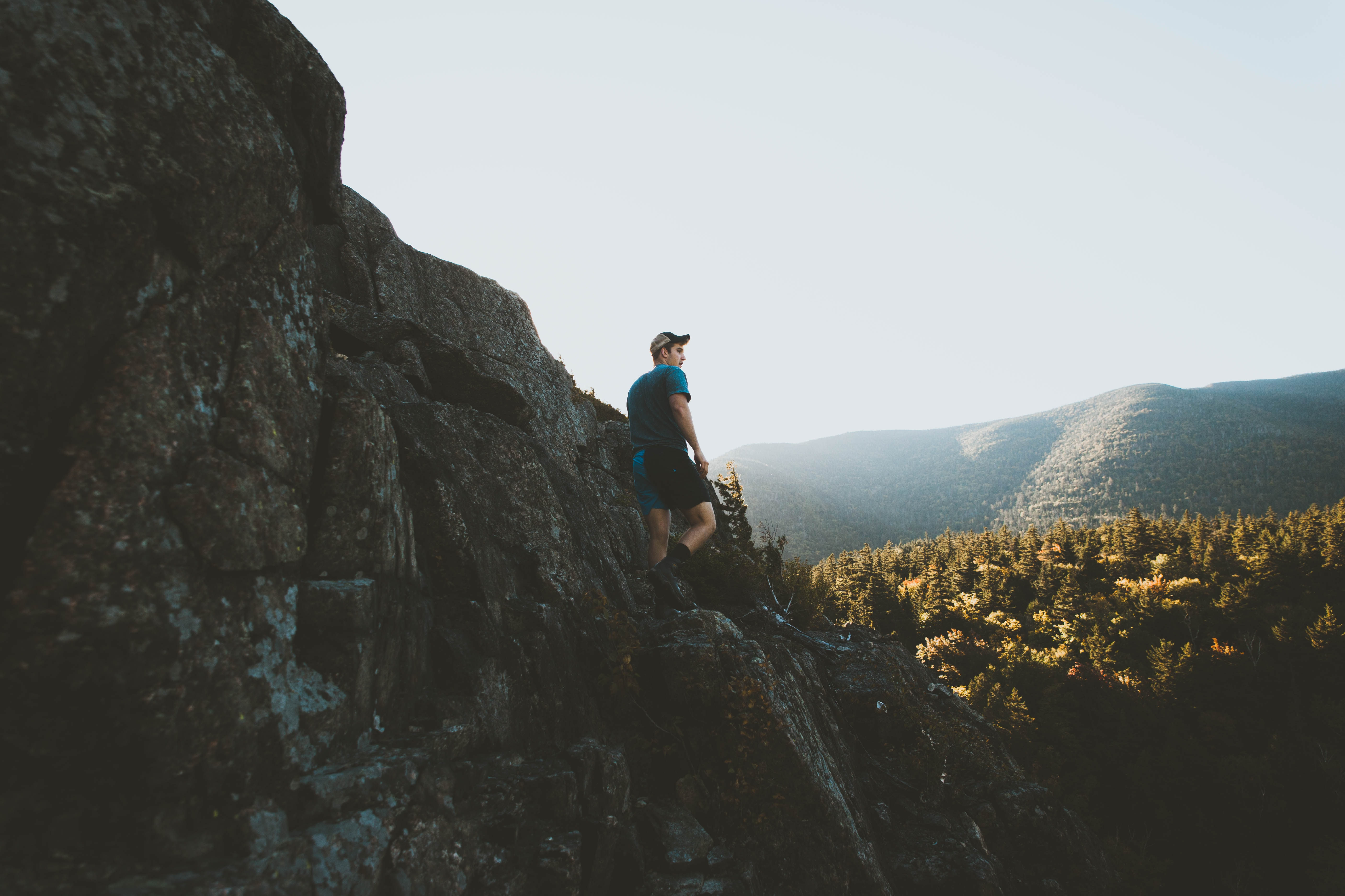A young man in a cap on a jagged rock formation in a morning