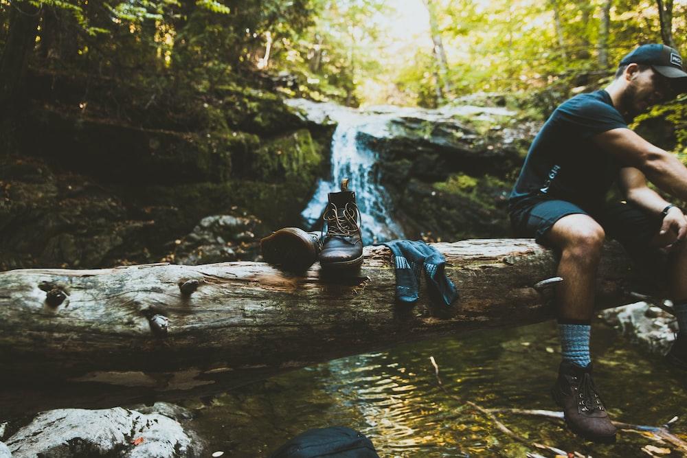 man sitting on tree log beside boots