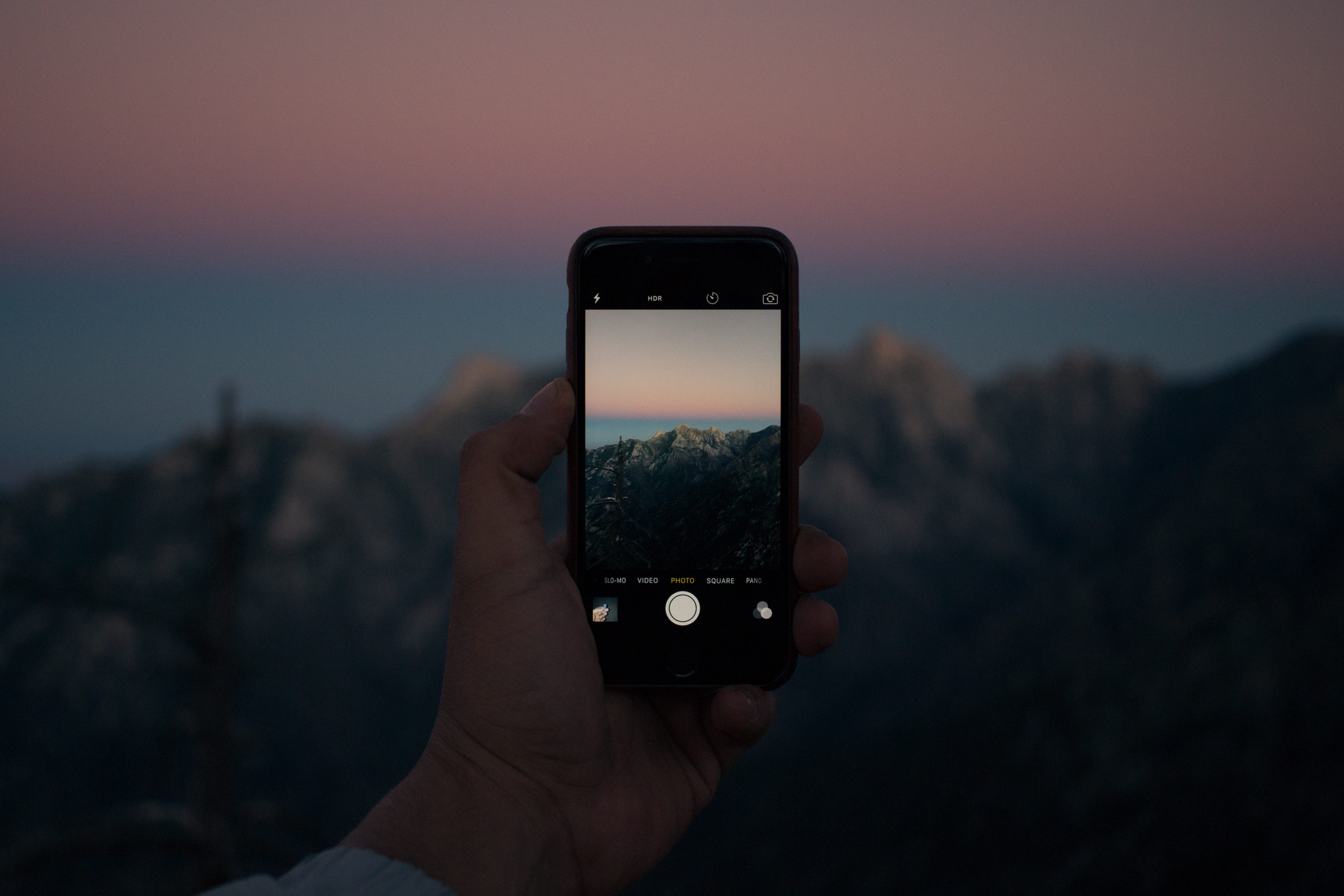 selective focus photography of person taking photo using iPhone