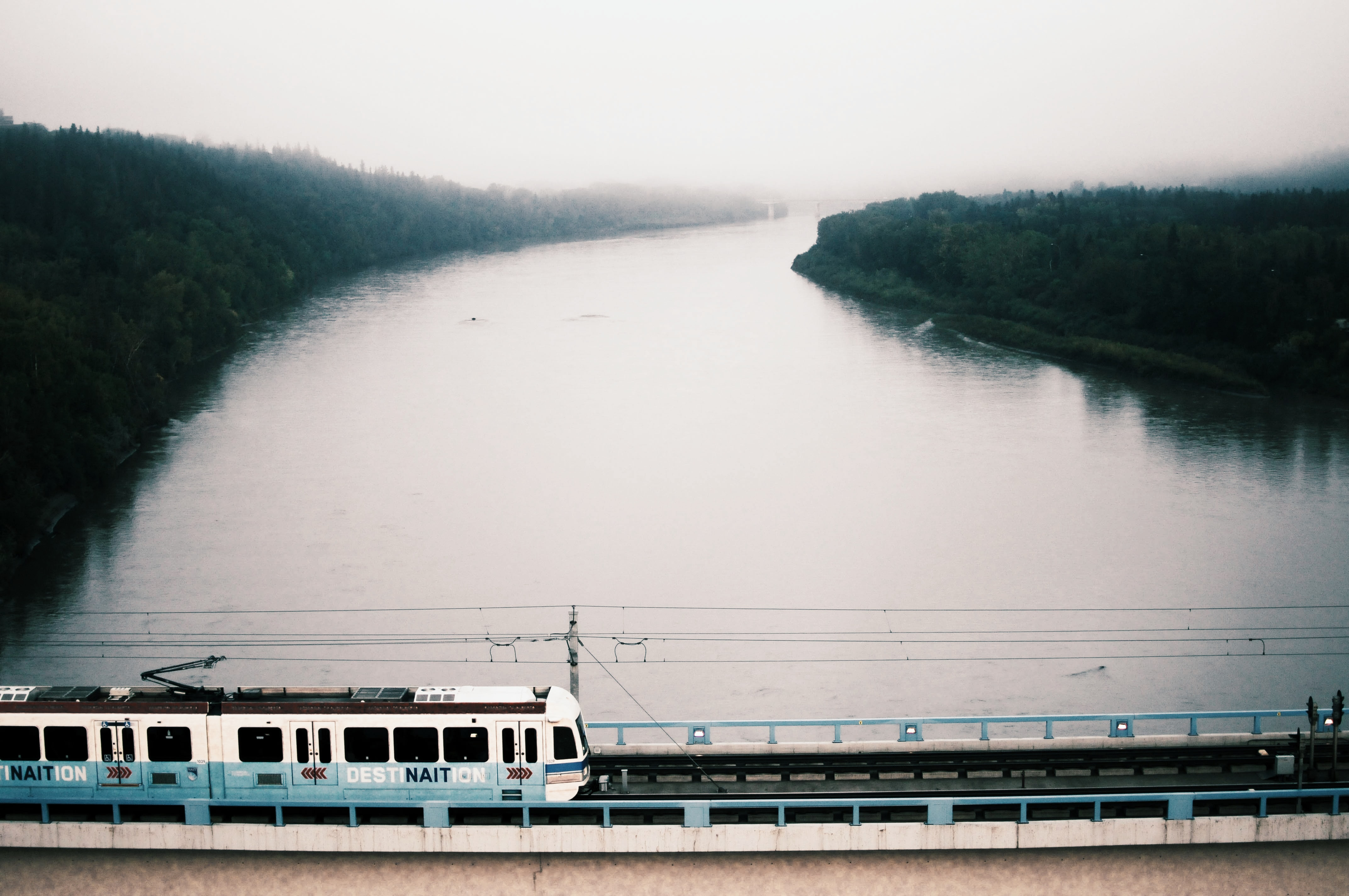 Public transport train on a bridge crosses the river on a misty and cloudy day