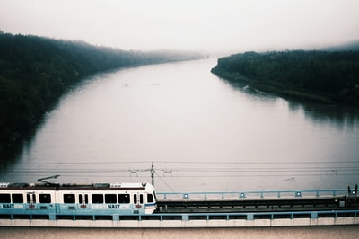 white train on bridge over river during daytime