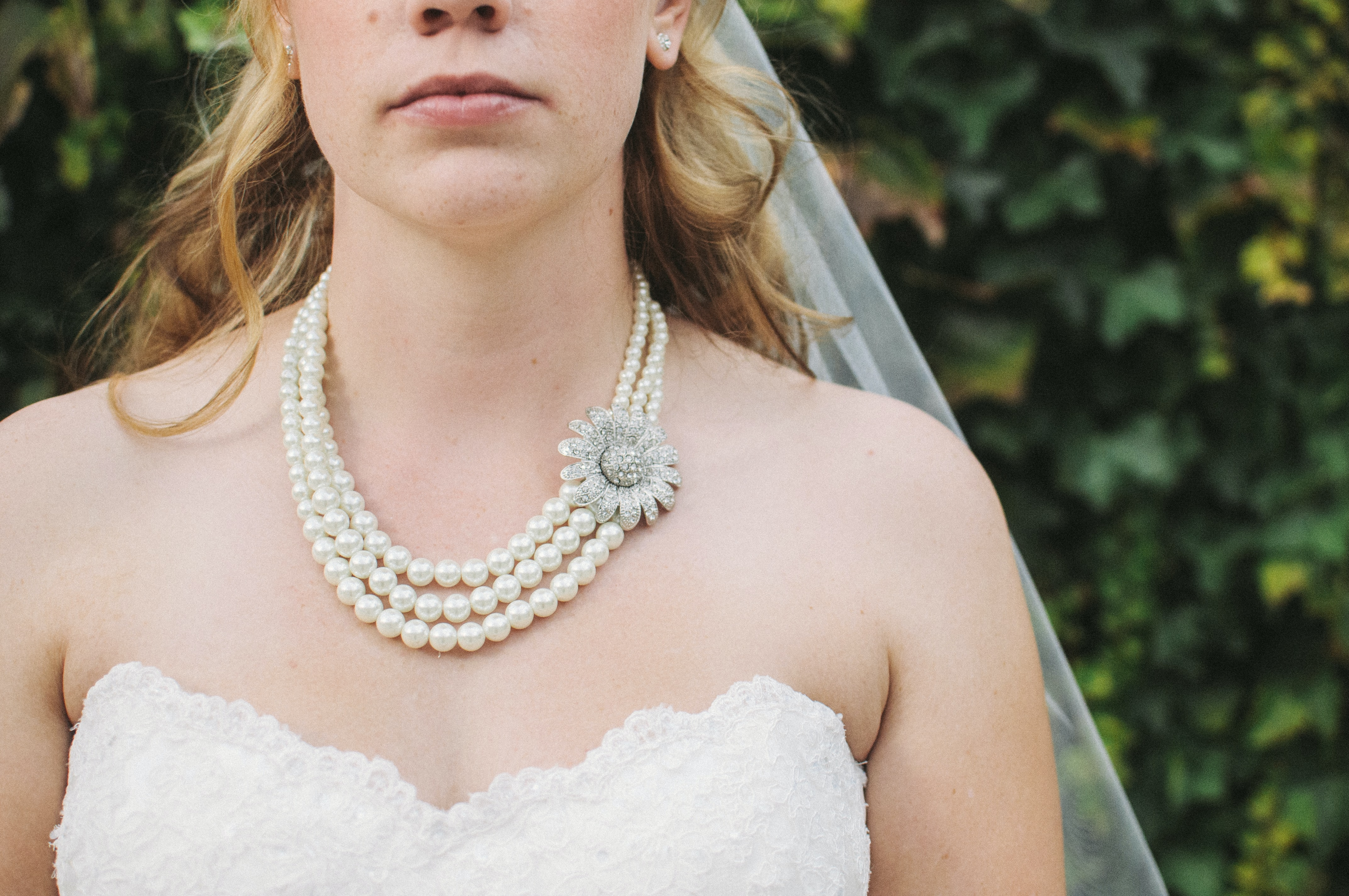 A close-up of a bride's chest, showing her wedding dress, veil, and pearl necklace
