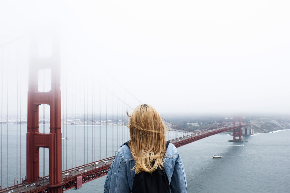 woman facing Golden Gate Bridge
