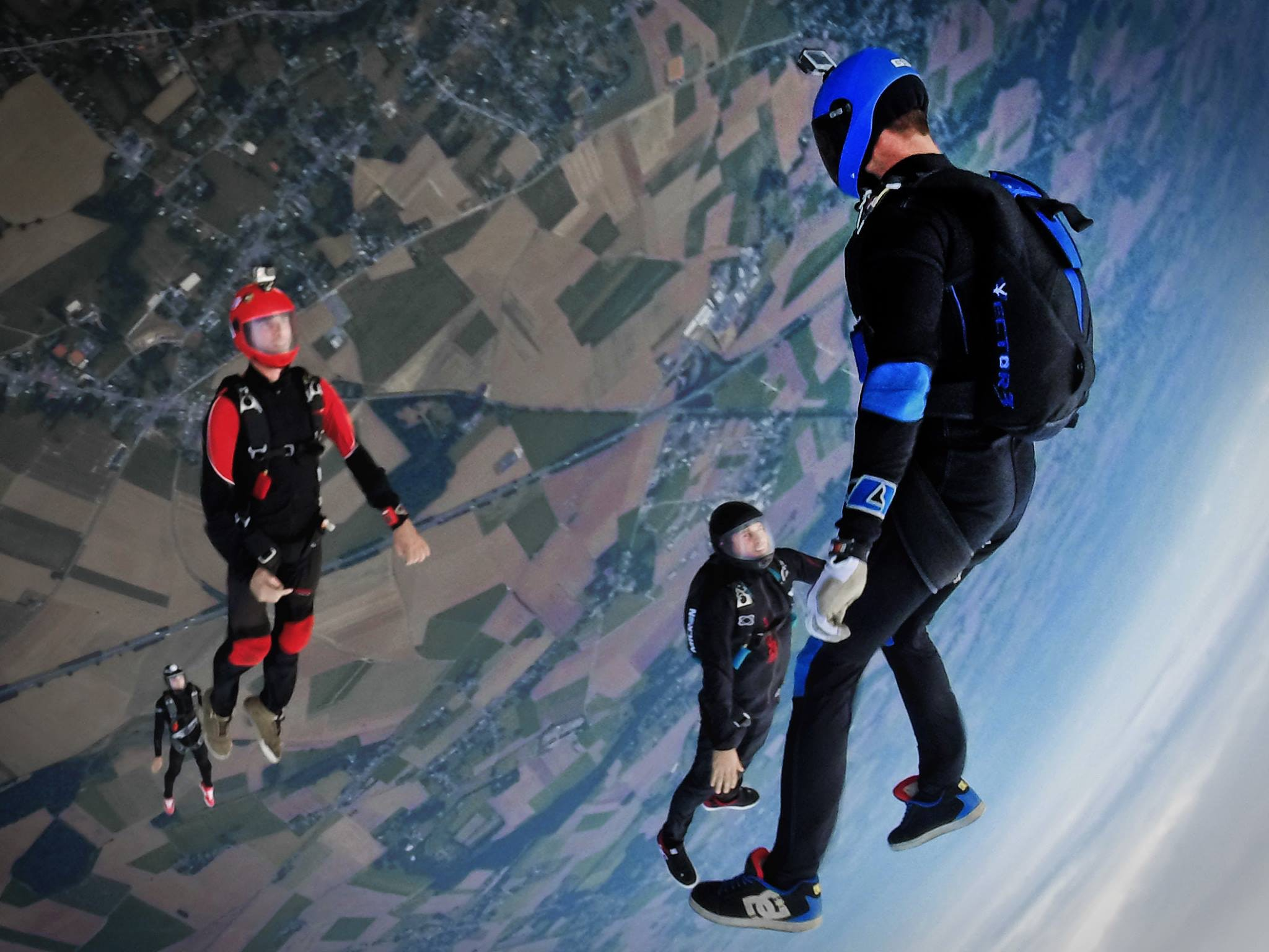 Four people skydiving wearing either red or blue suits at Para Club Aérodrome de Namur