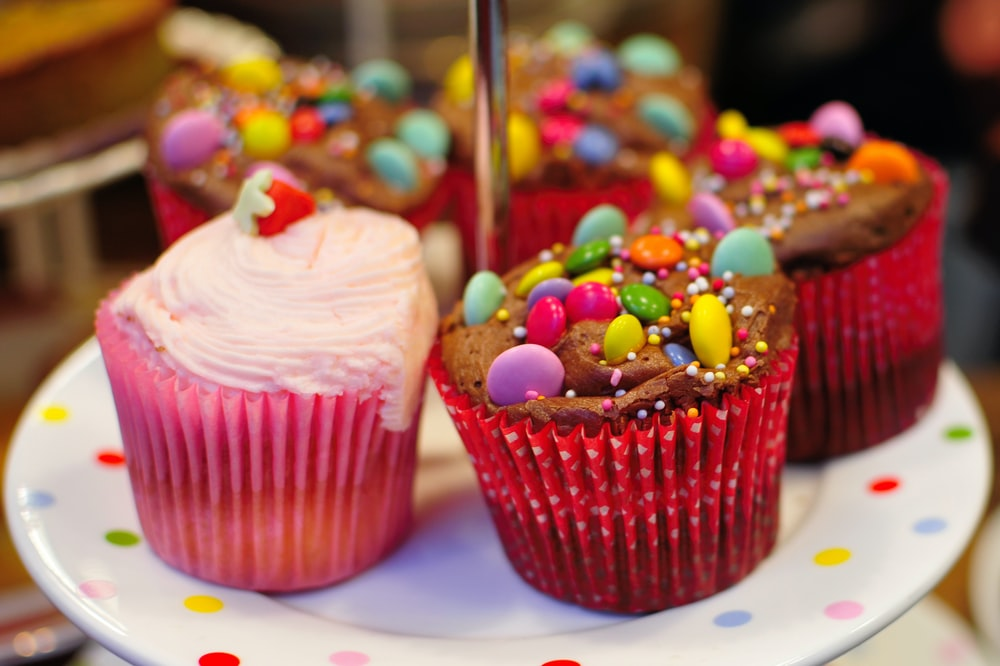 A plate with cupcakes topped with cream and candy