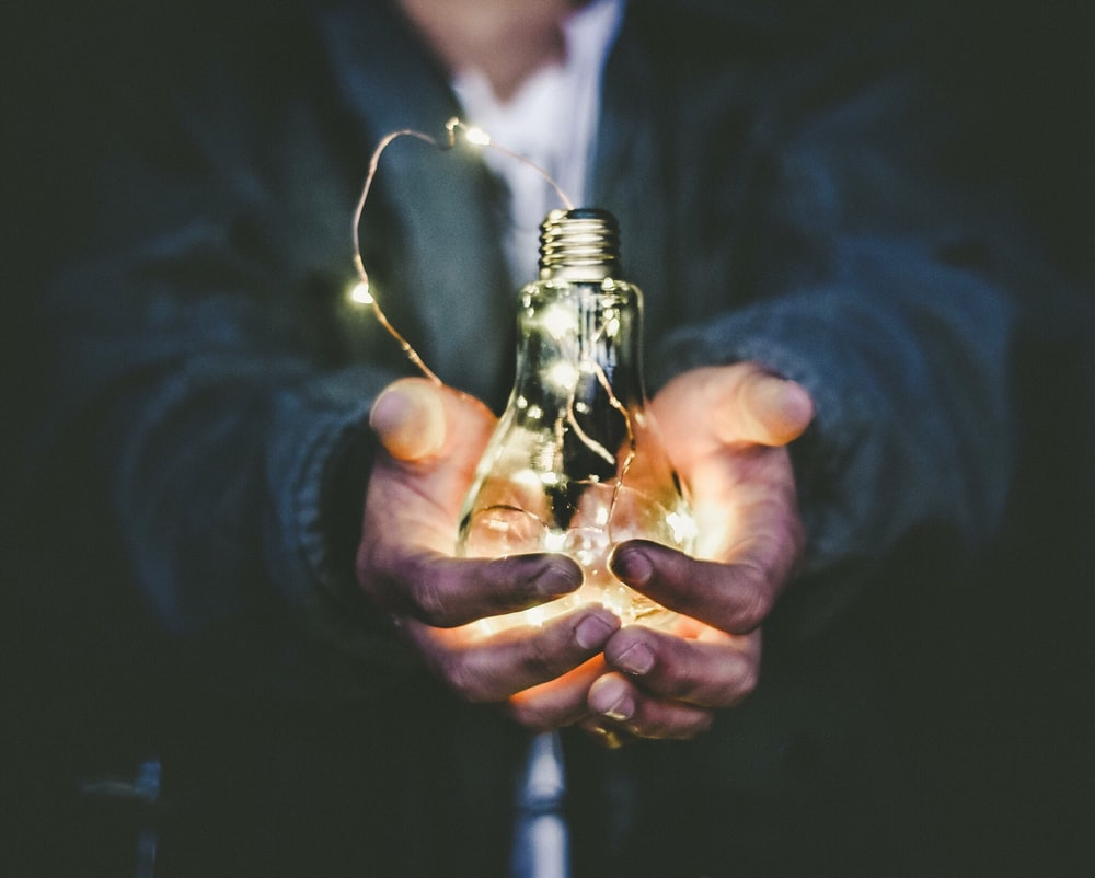man holding incandescent bulb