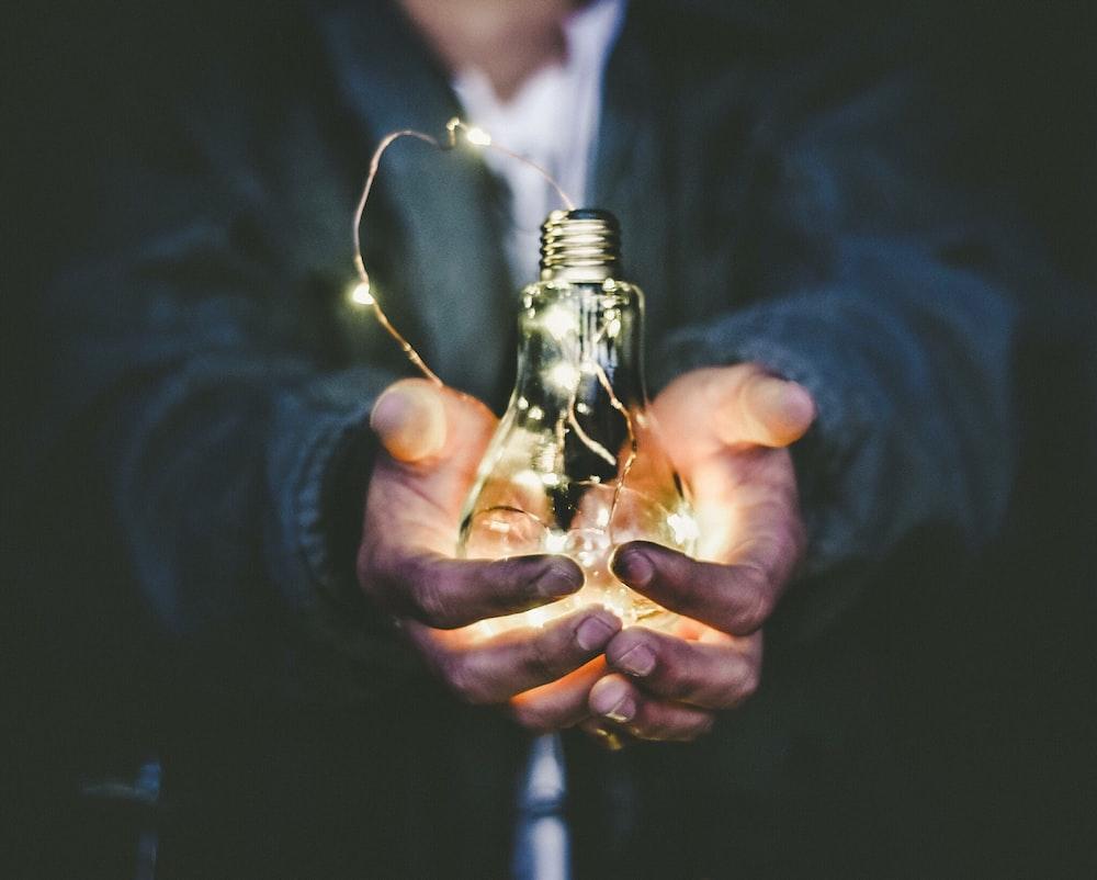 man holding incandescent bulb