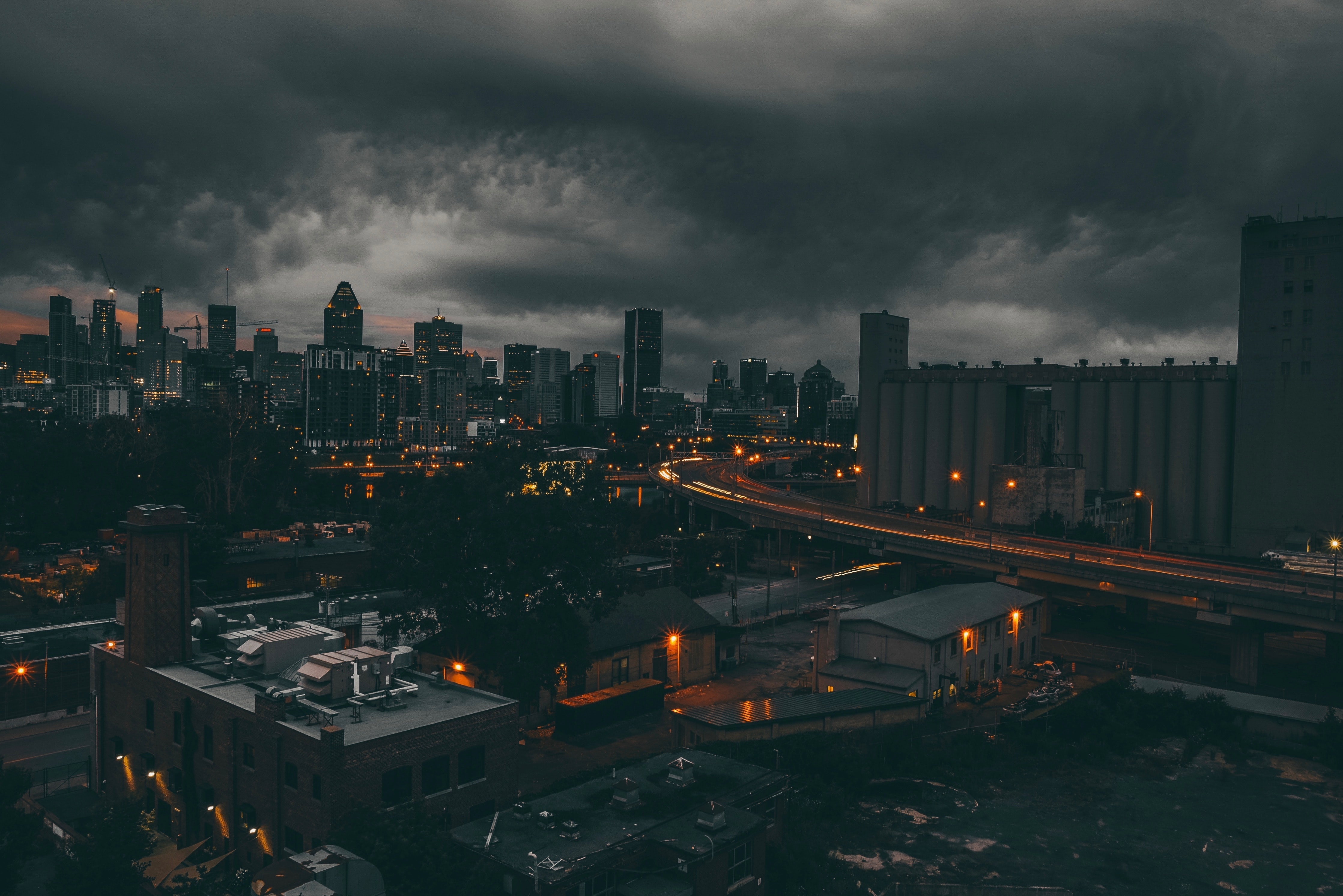 time-lapse photography of city under black cloudy sky