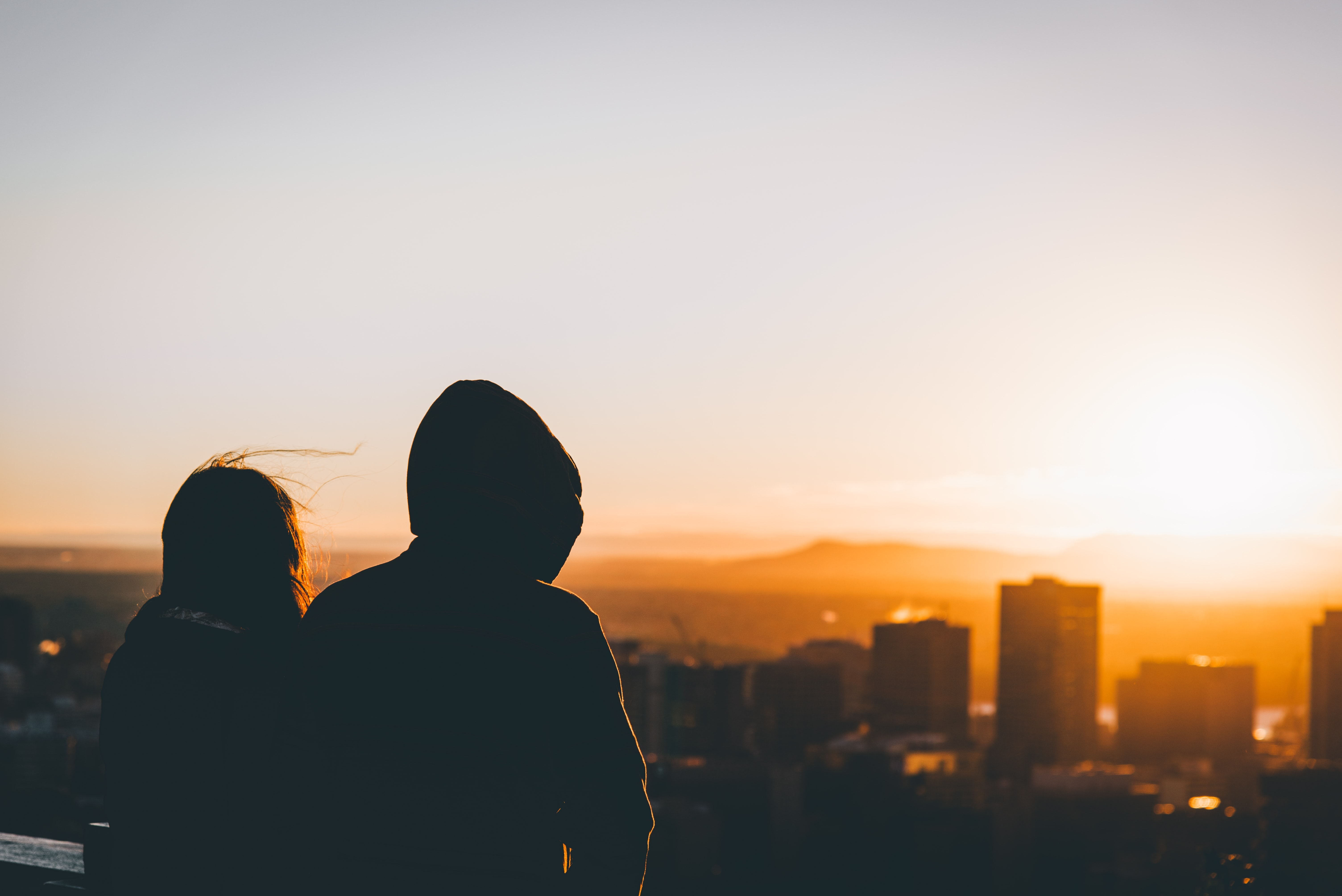 Silhouettes of two people looking over a cityscape during sunset