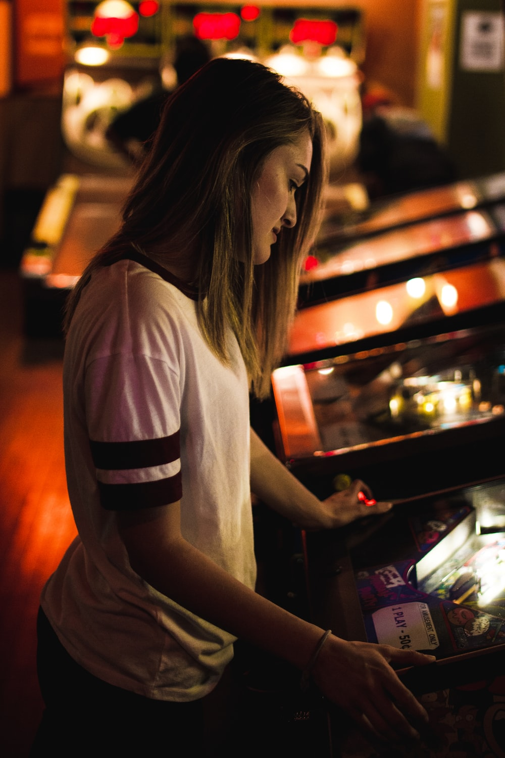 woman in white and black shirt standing in front of arcade machine