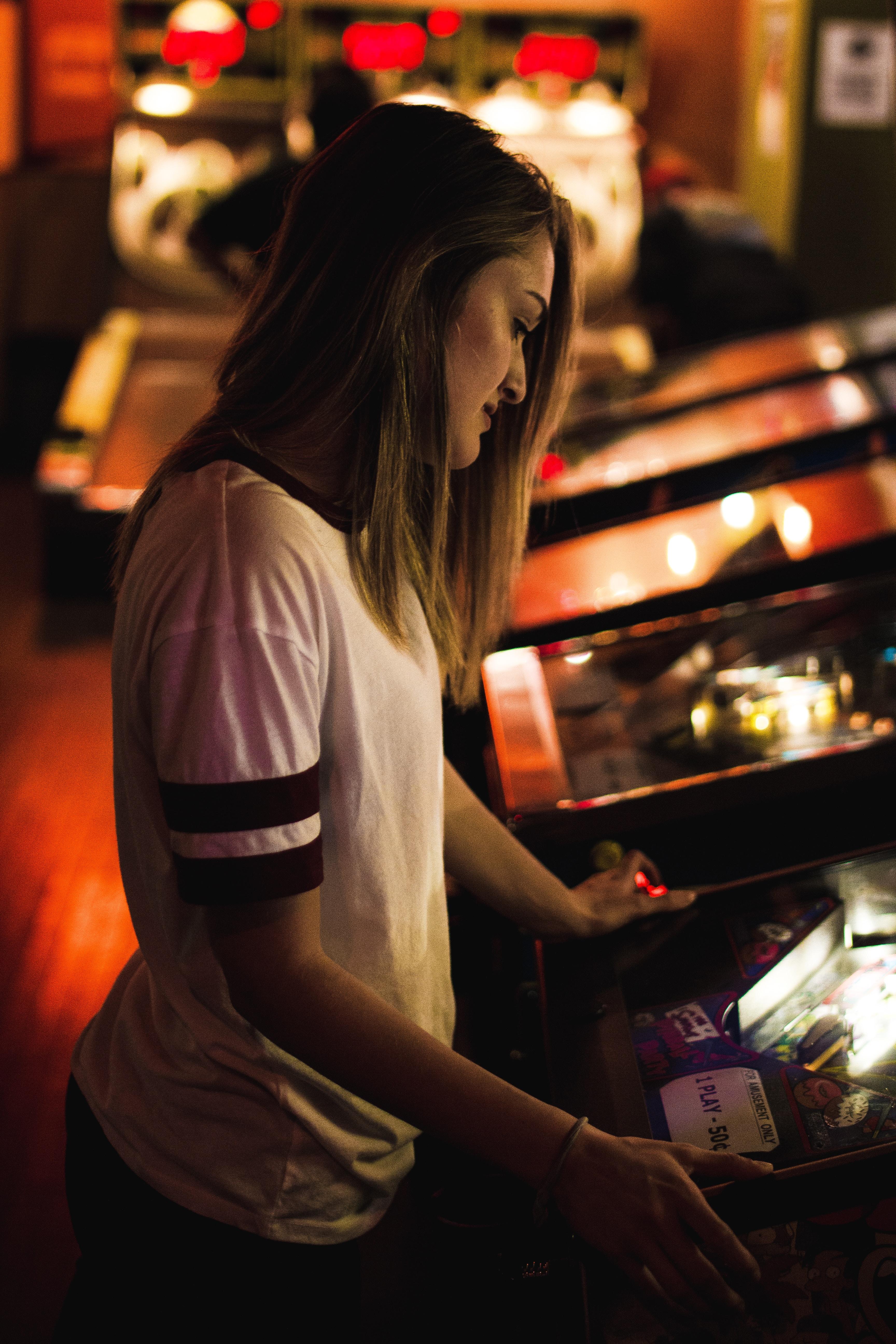 A woman with medium-length brown hair plays a game in an arcade