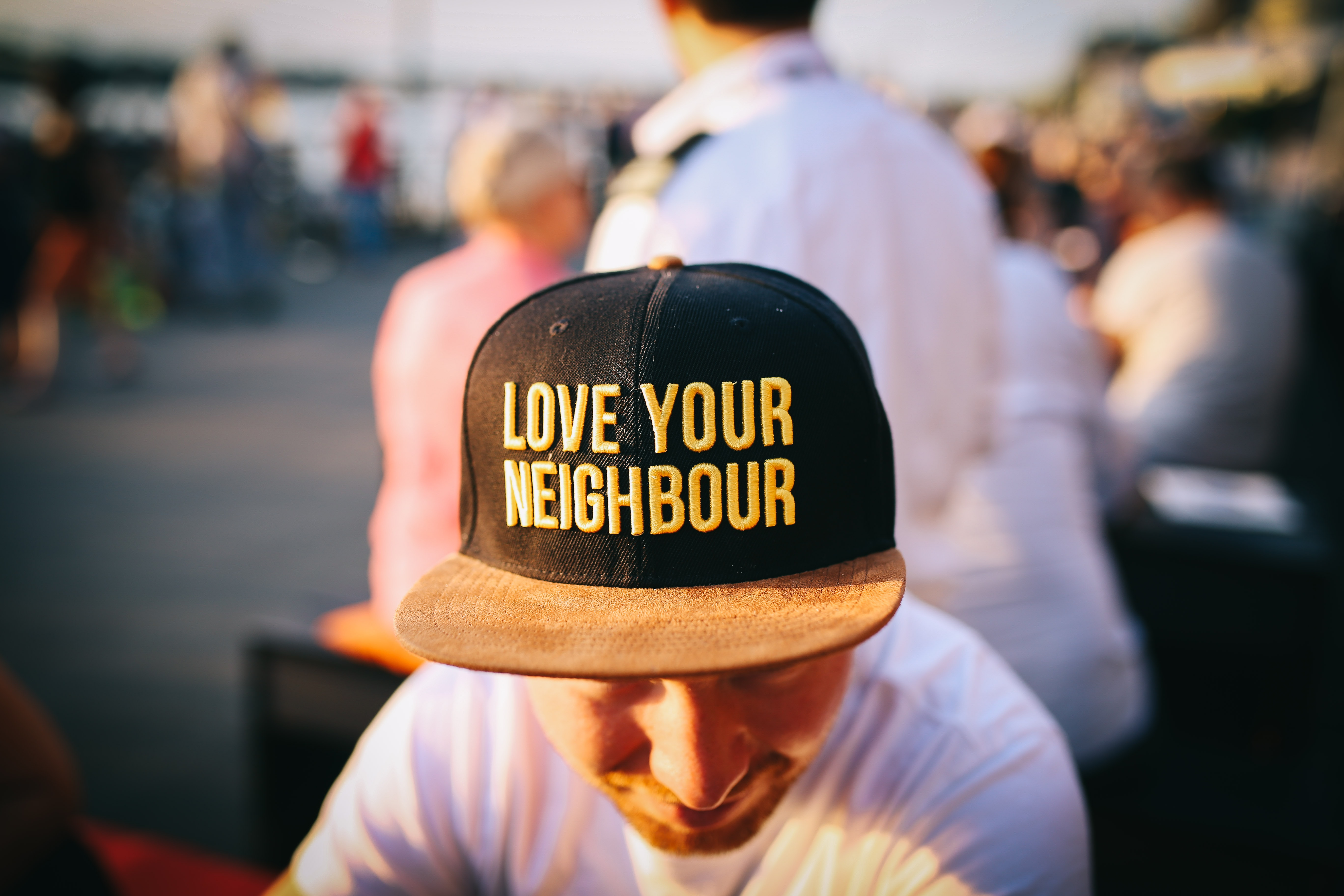 "A man wears a hat that reads ""Love Your Neighbour"" on crowded Rheinpromenade"