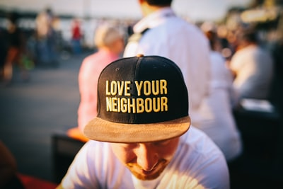 man wearing black cap with love your neighbour print during daytime humanity teams background