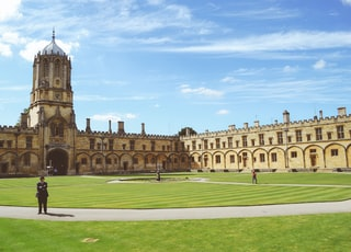 three person standing on university grass field