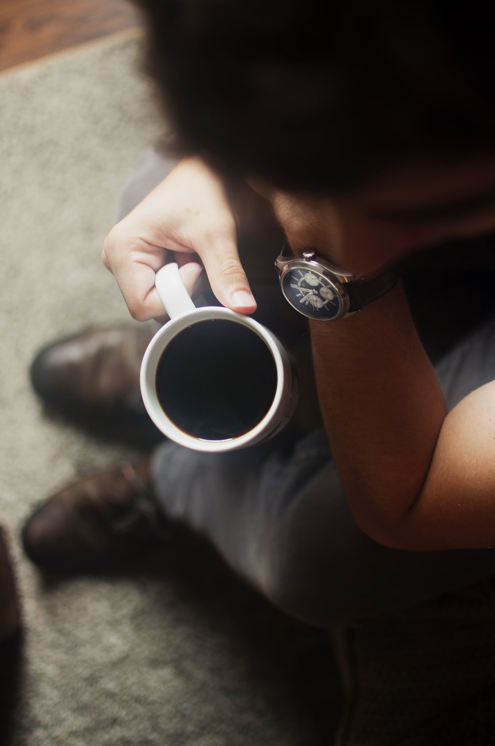 person sitting on couch holding coffee mug