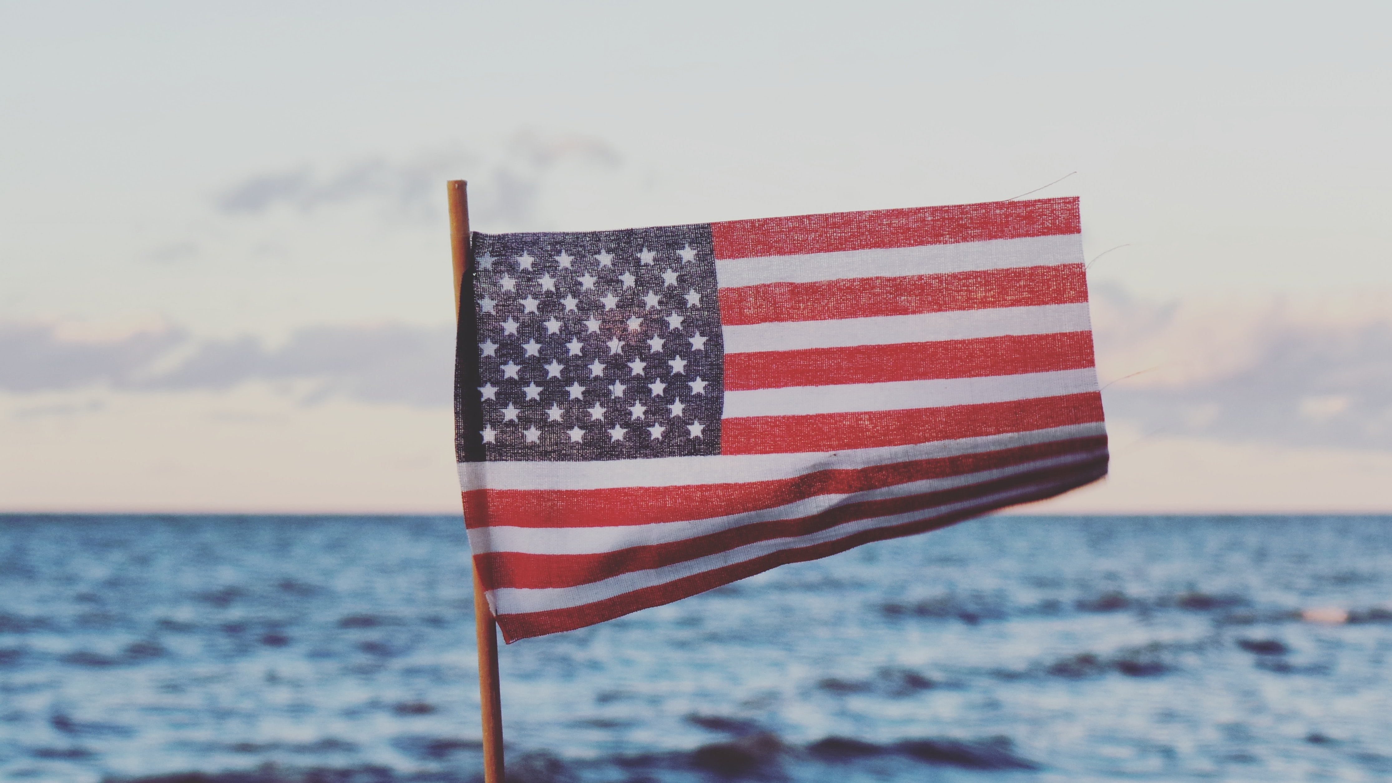 The macro view of the flag of the USA waving as the wind blows with a sea behind it.
