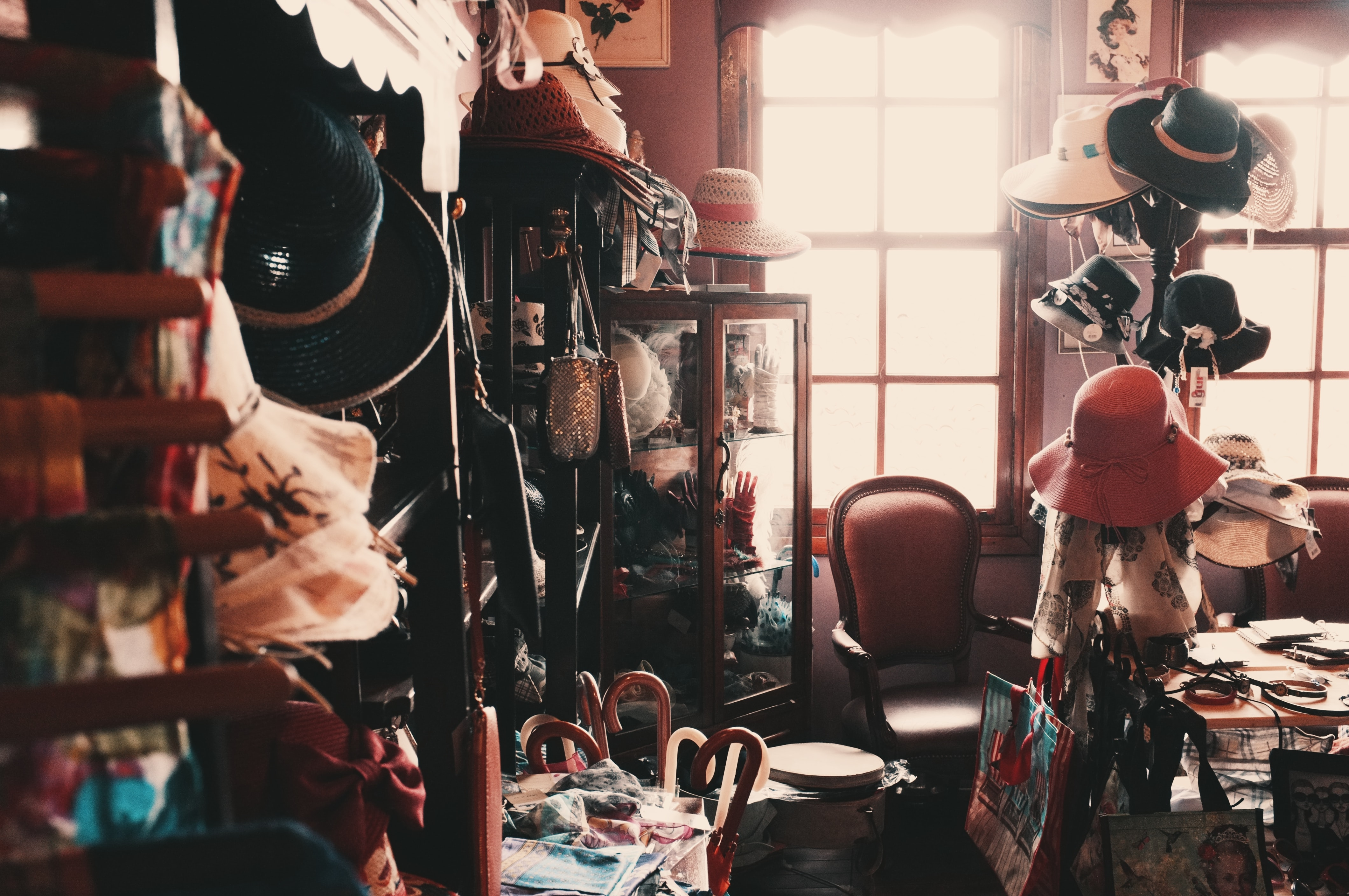 The interior of a vintage store full of various hats and accessories