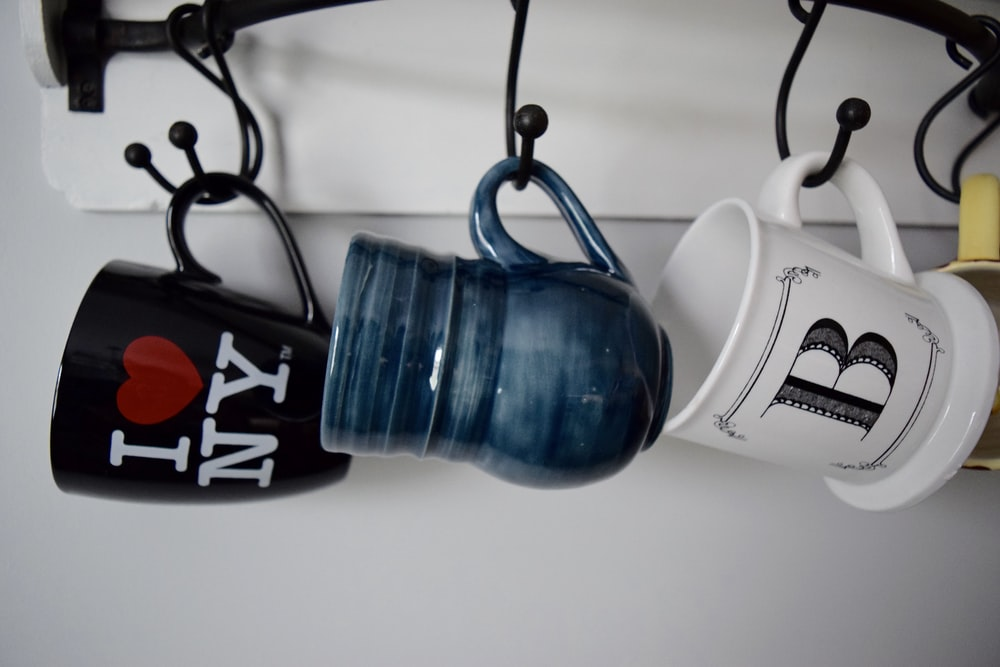 three hanged assorted-color ceramic mugs