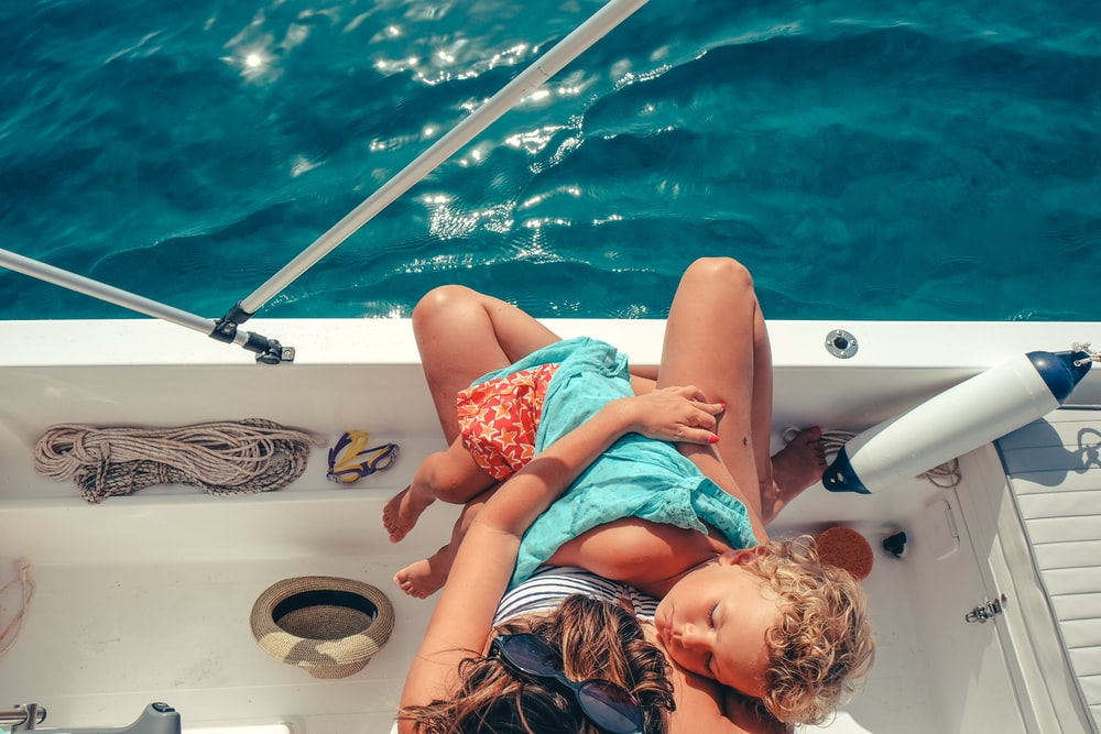 toddler lying on person's body while riding on white boat