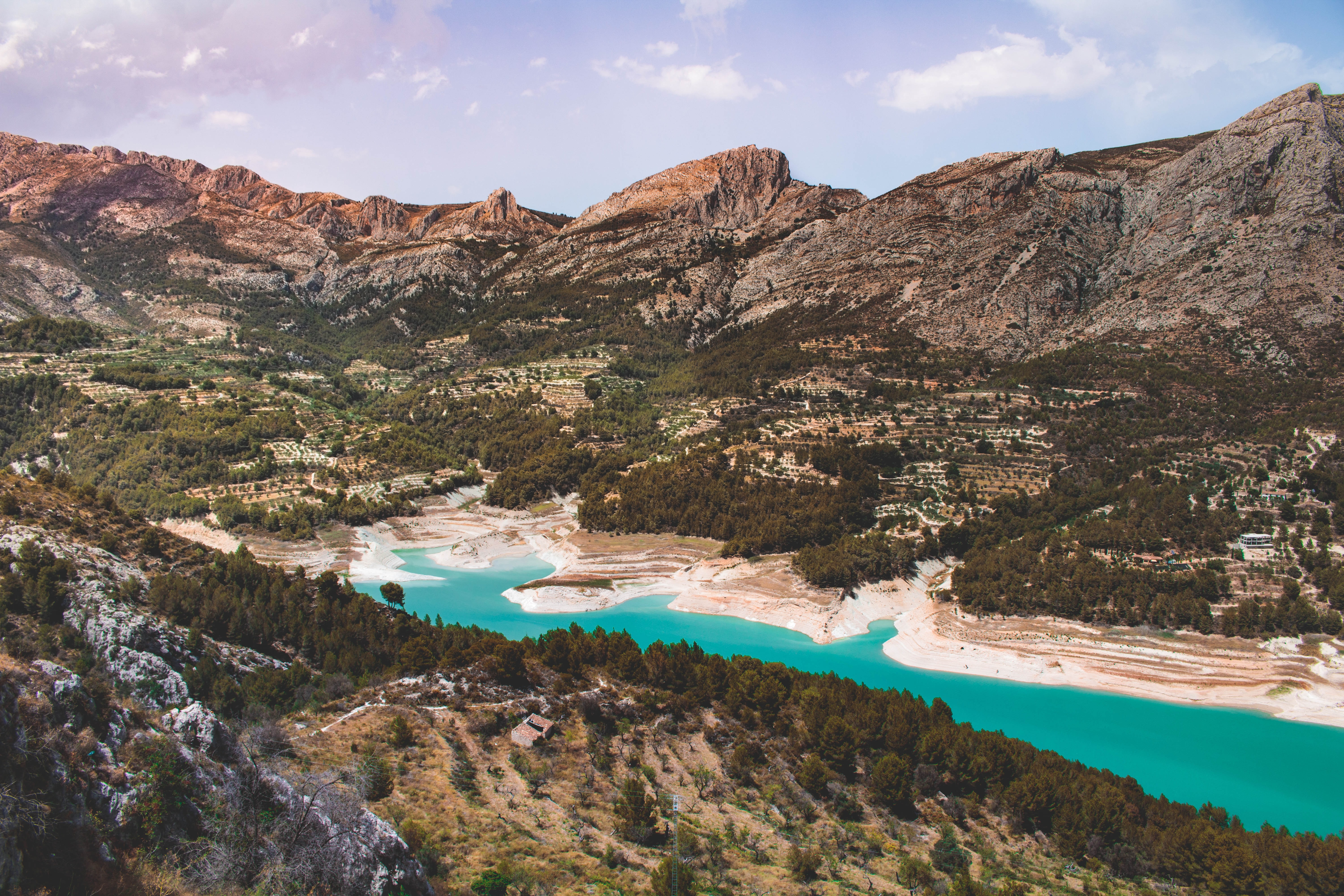 A blue lake surrounded by low mountains on a sunny day in Guadalest