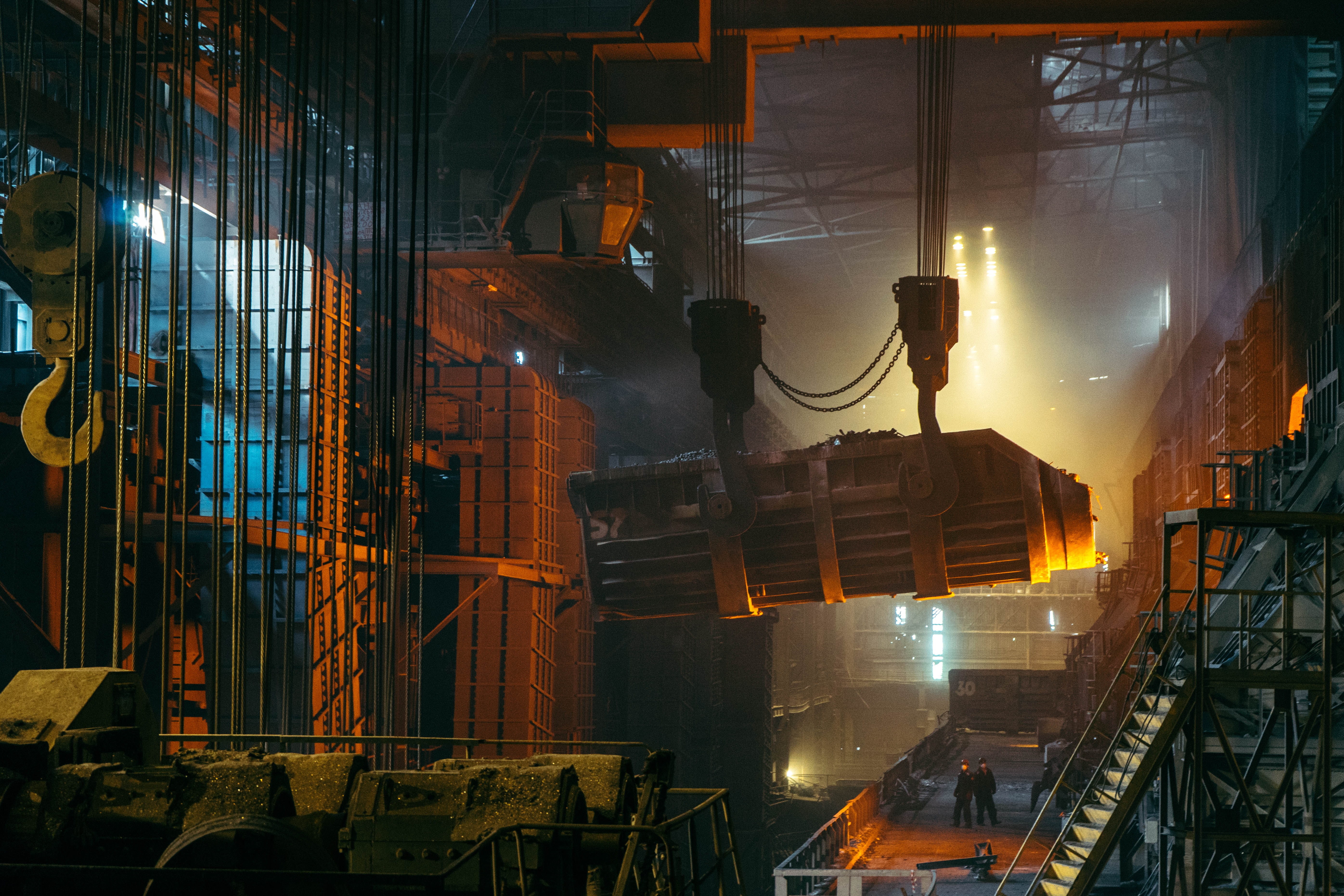 Two men in a steelworks with a crane moving the material over their heads