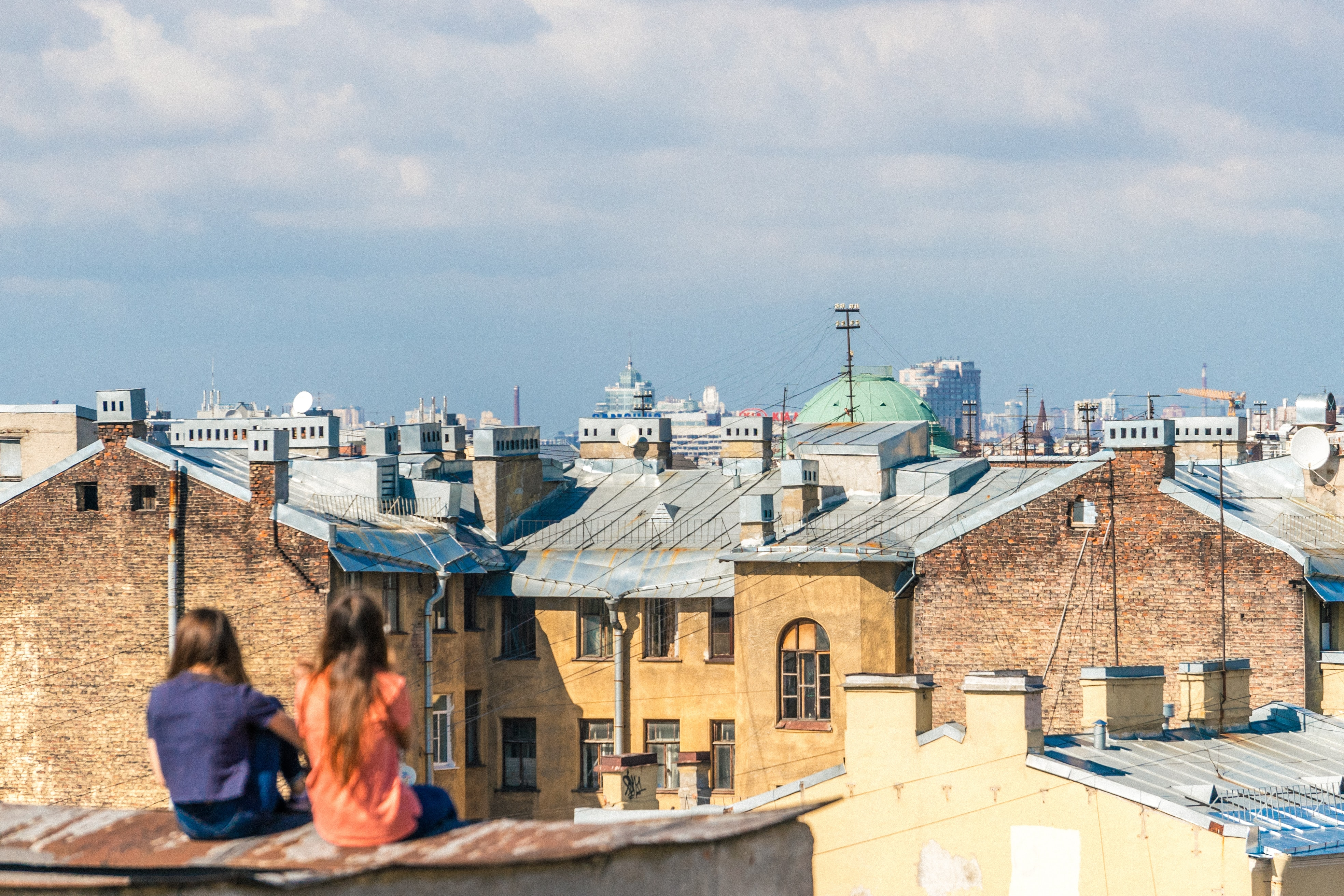 two women sitting on roof overlooking building during daytime