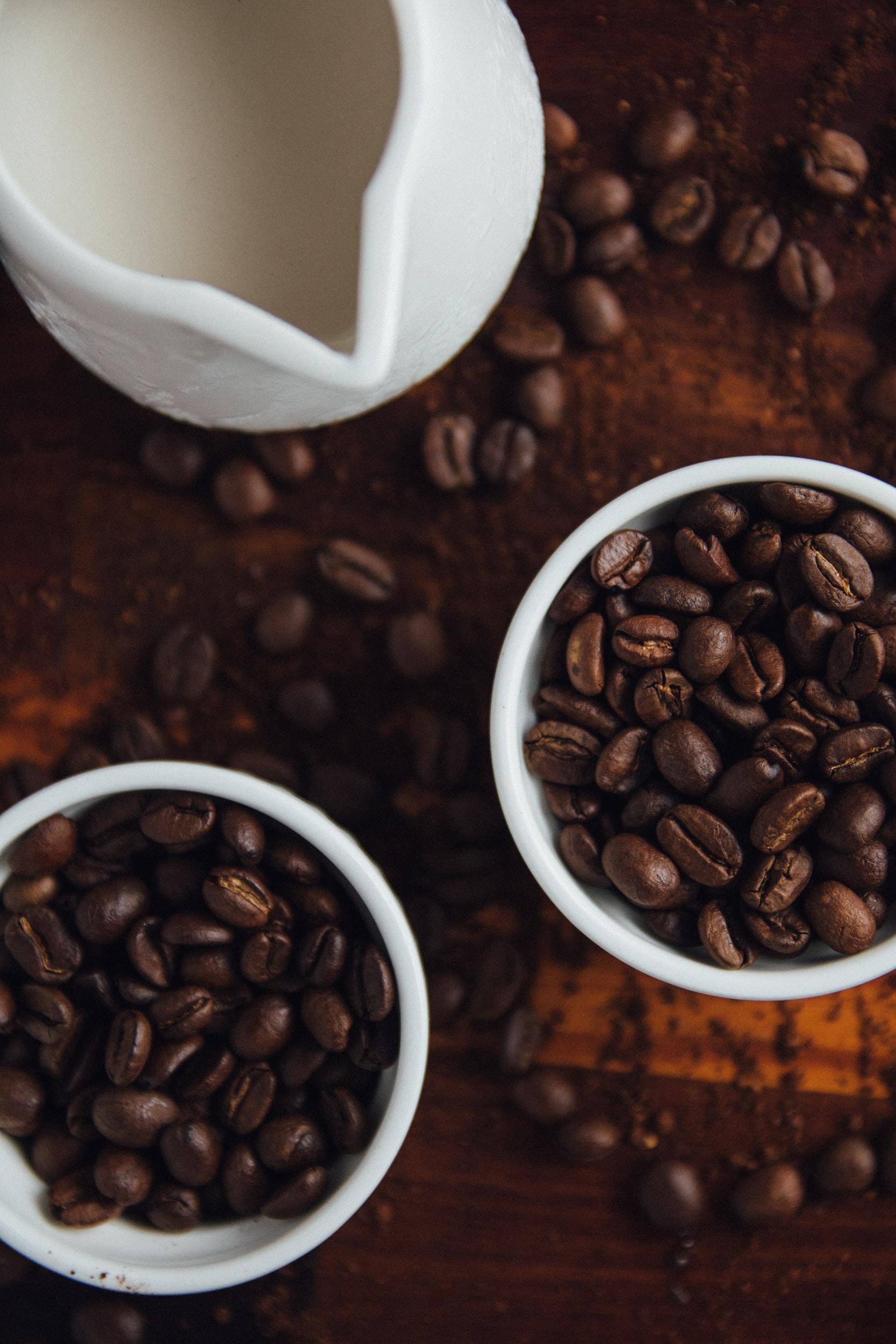 black coffee beans in ceramic mugs