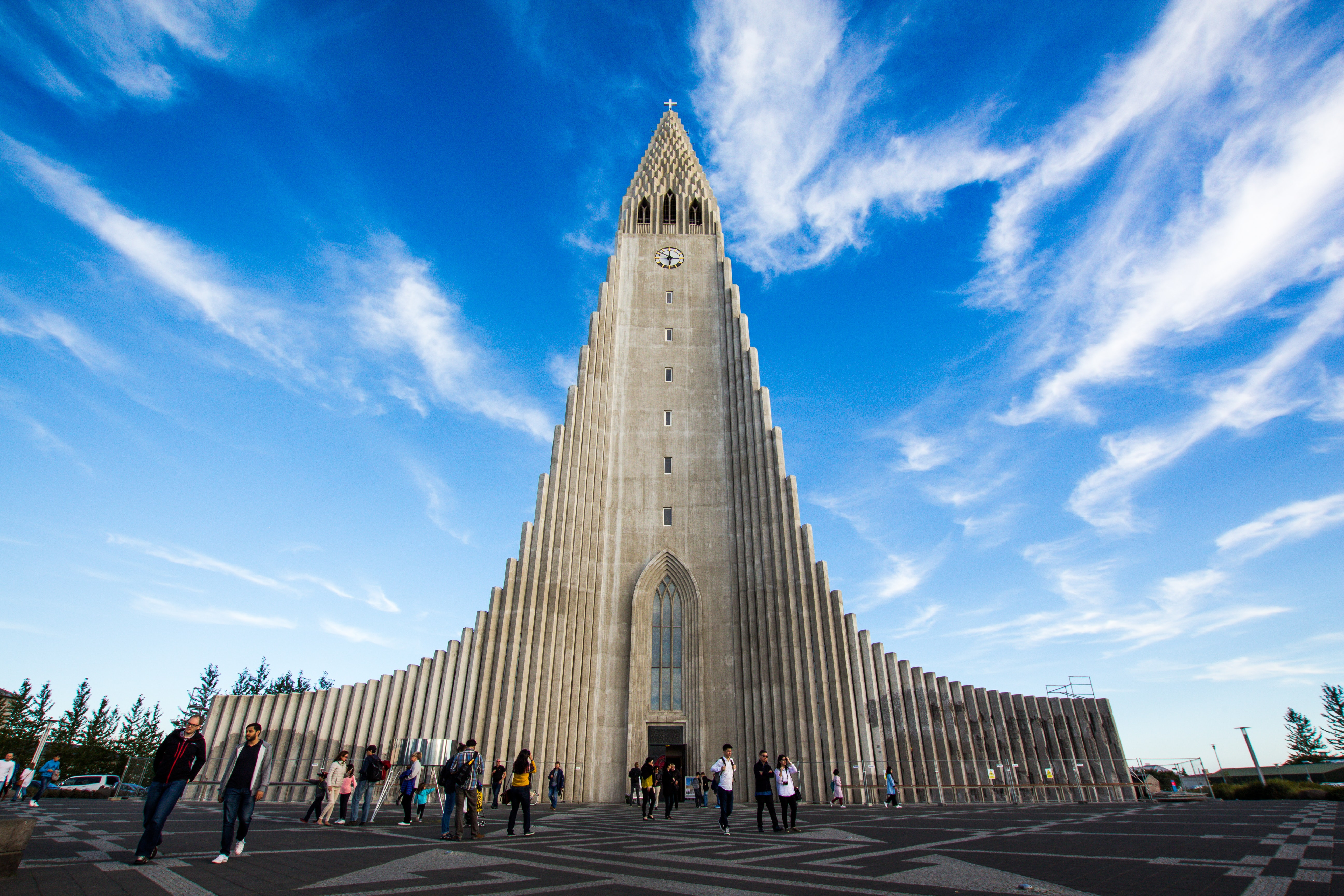 A group of people is standing in front of the Hallgrimskirkja Church.