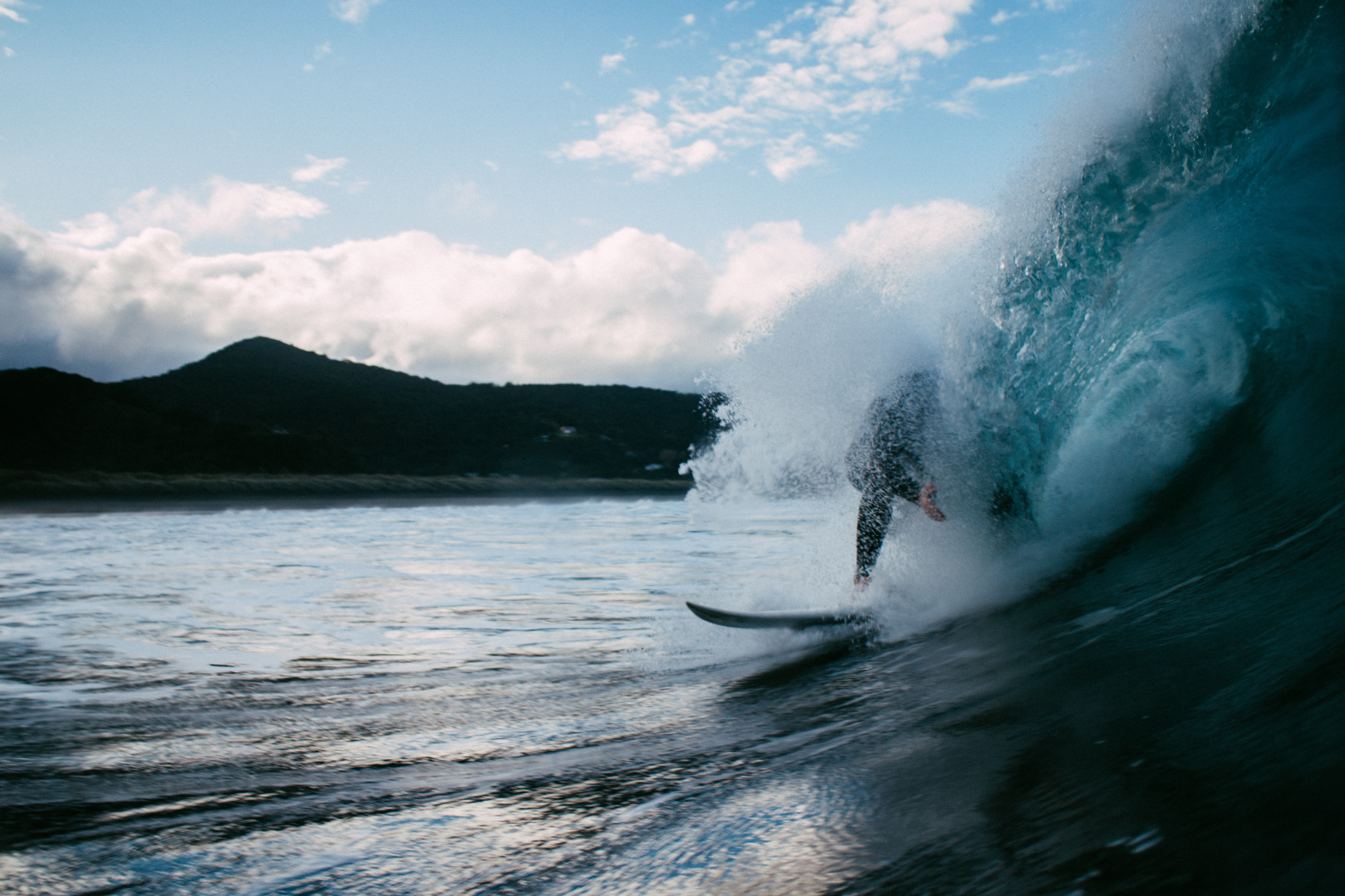 Surfer surfing on the wave at Piha Beach