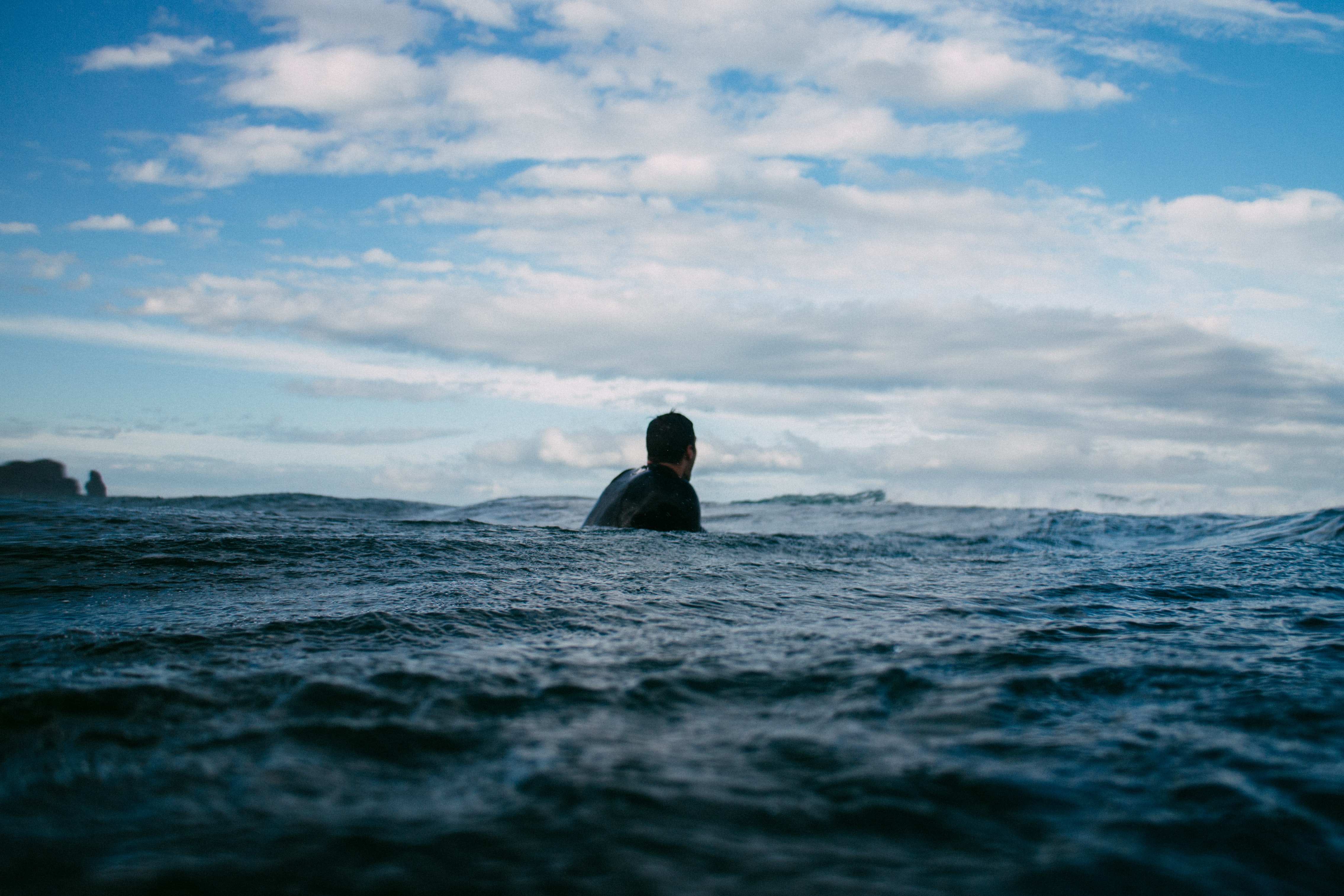 Person floating in the ocean at Piha Beach