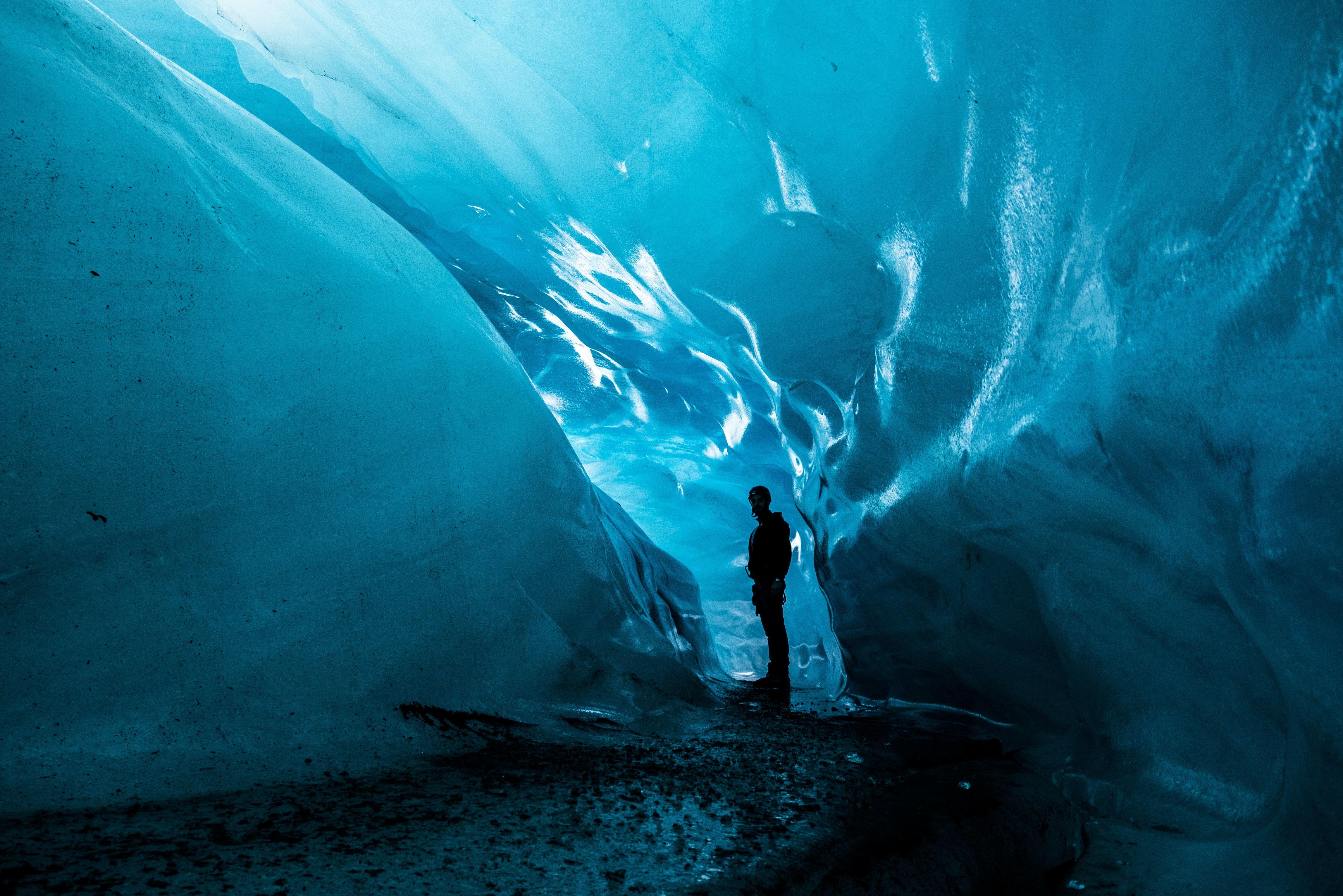 person standing in ice cave at daytime
