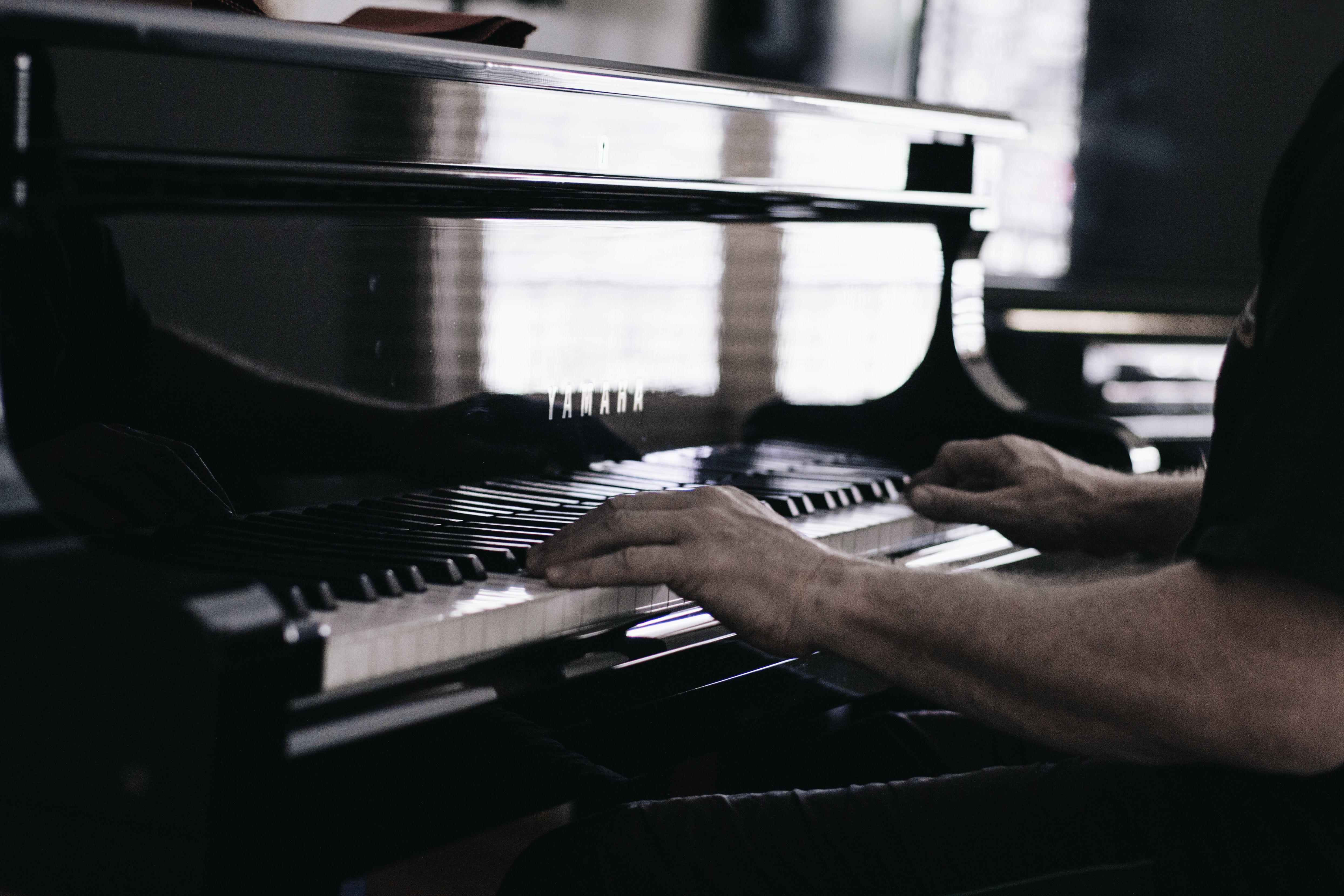 A fuzzy shot of a man's hands on the keyboard of a piano