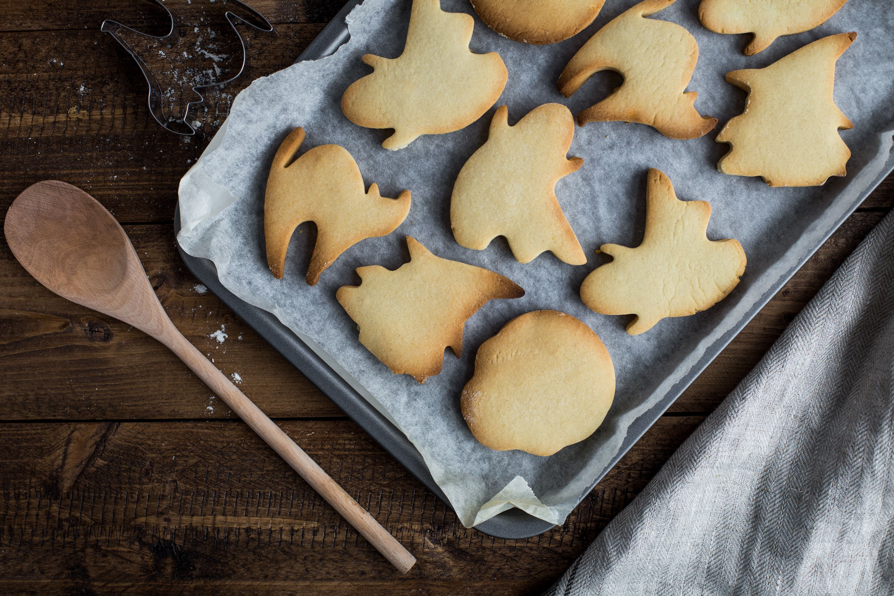 An overhead shot of a tray of baked cookies in the shape of cats, ghosts and witches