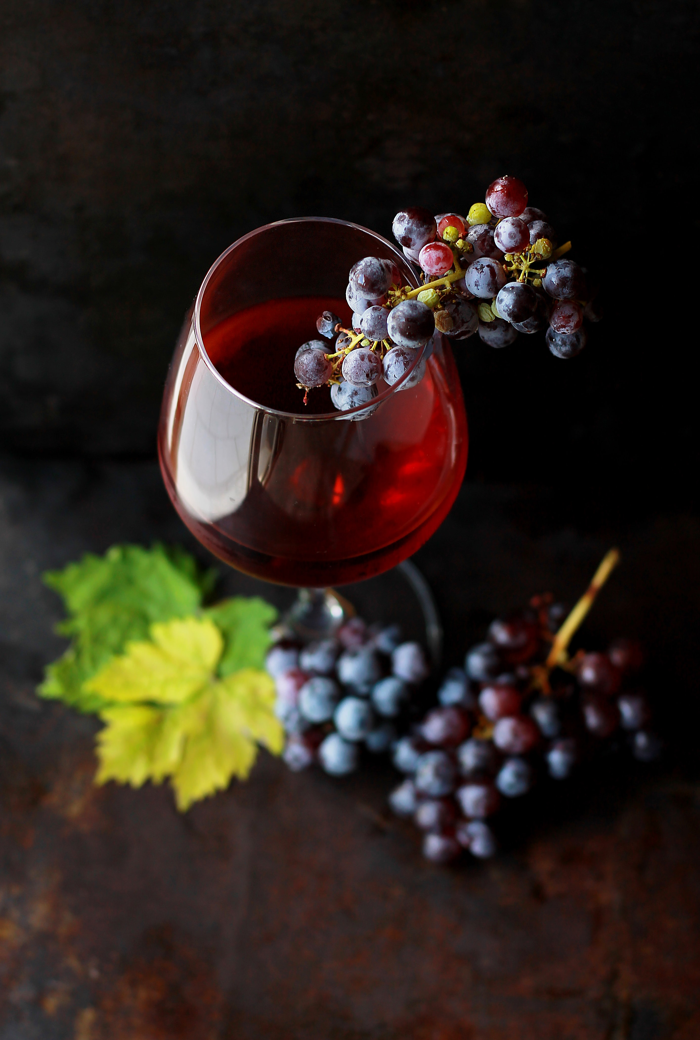 Macro view of a wine glass containing alcoholic wine with a bunch of grapes