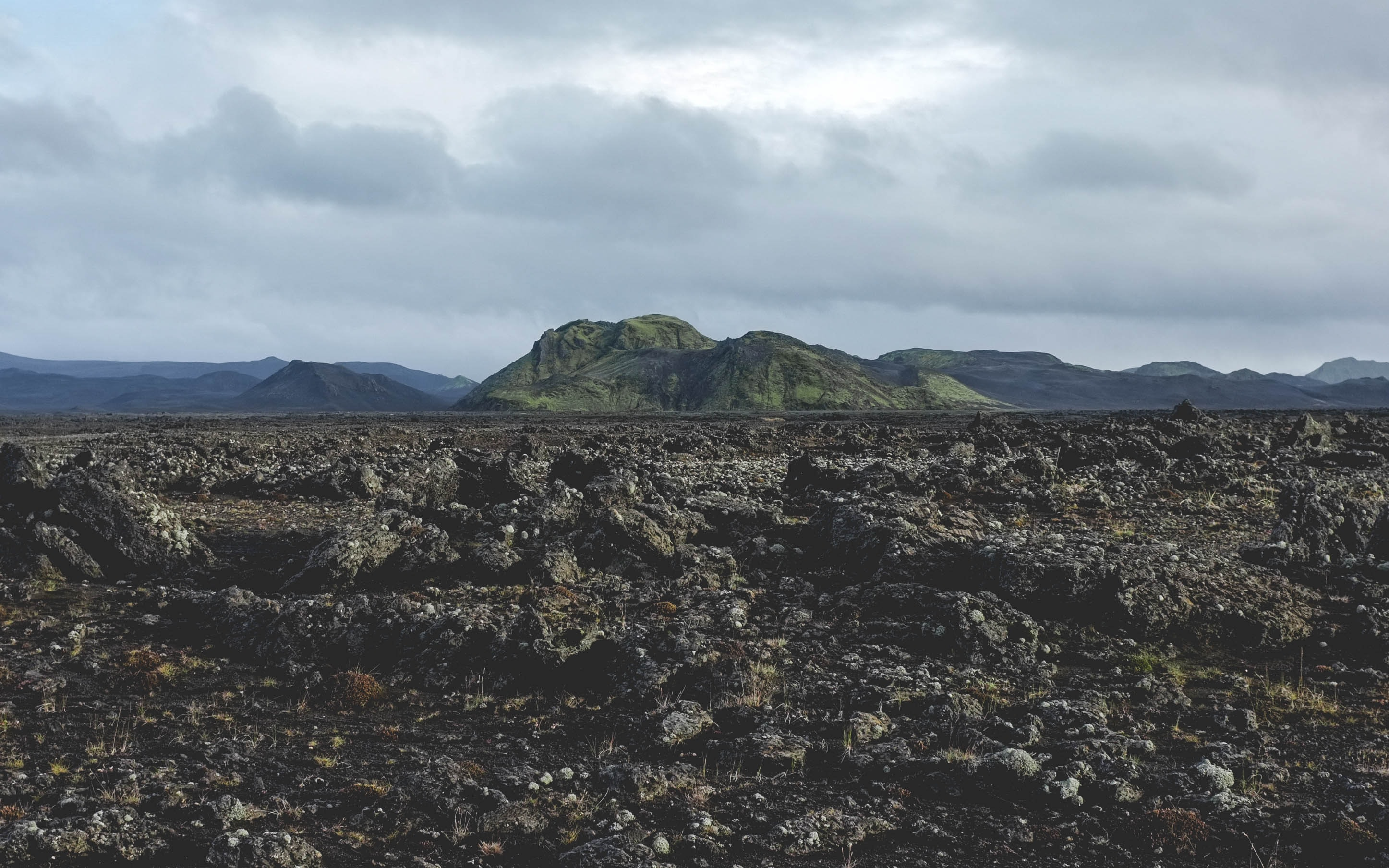 A rocky plain with low green mountains at the back on a cloudy day