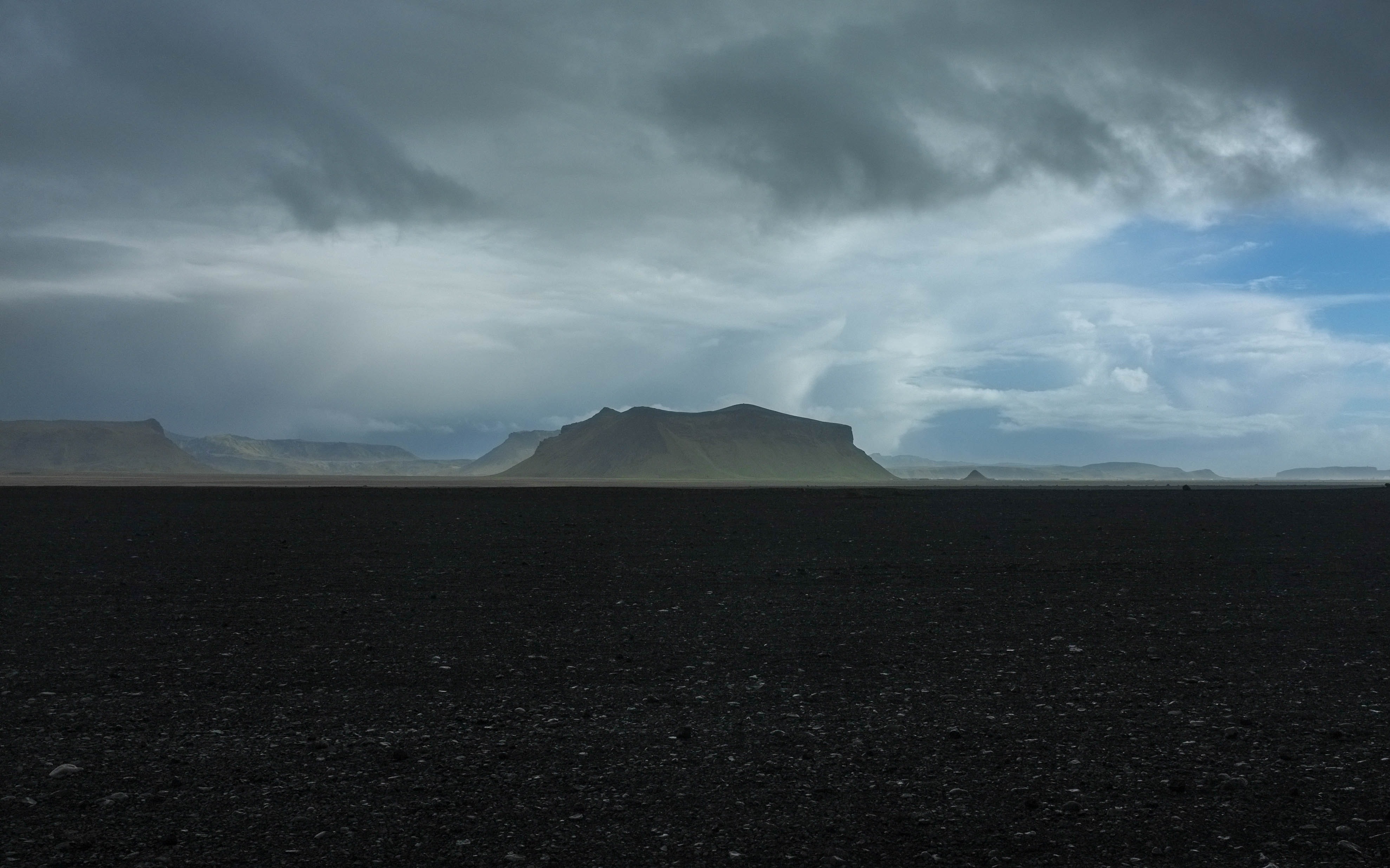 A rocky plain with flat mountains on the horizon on a cloudy day