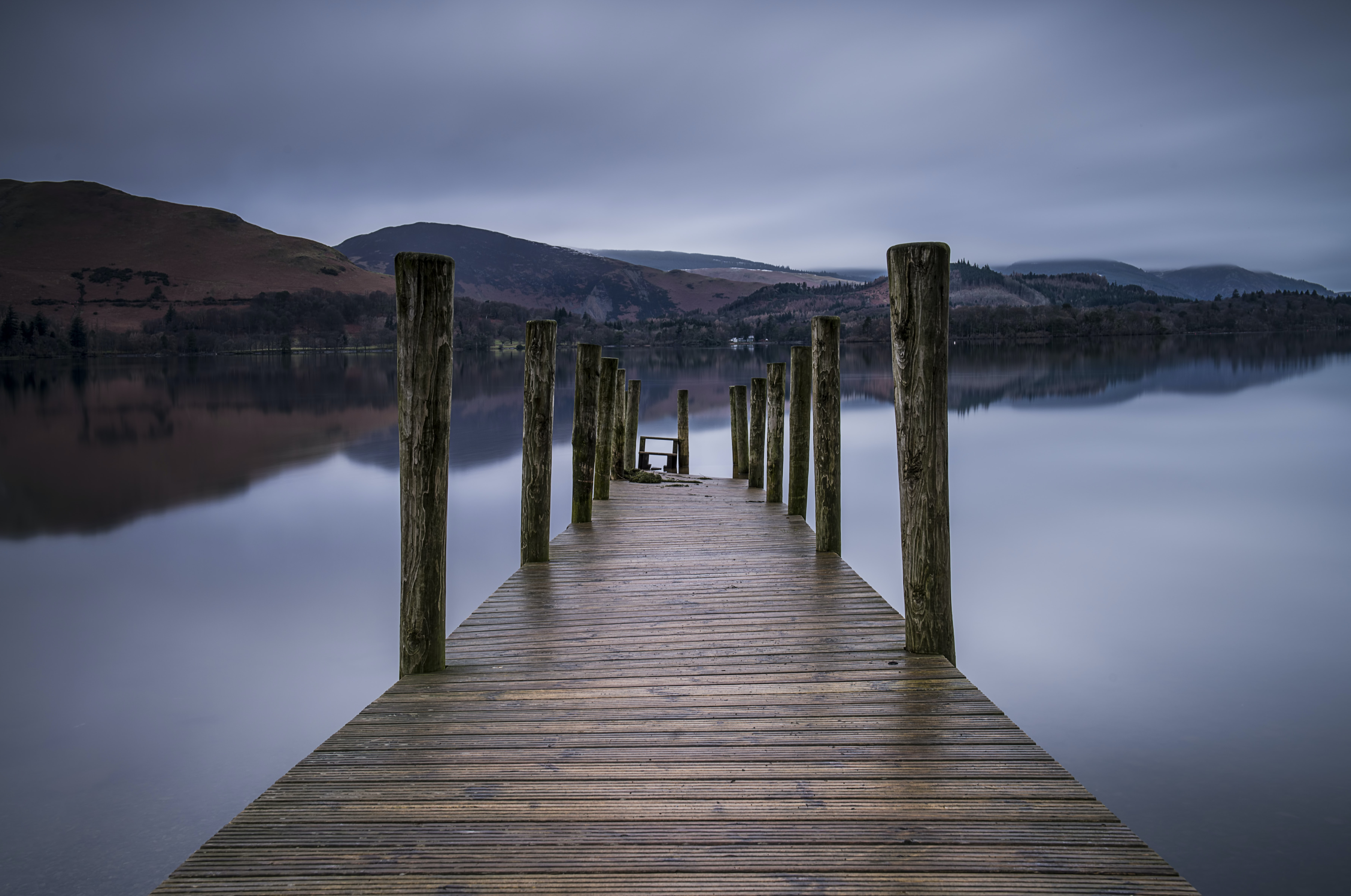 brown wooden dock on body of water overlooking mountains
