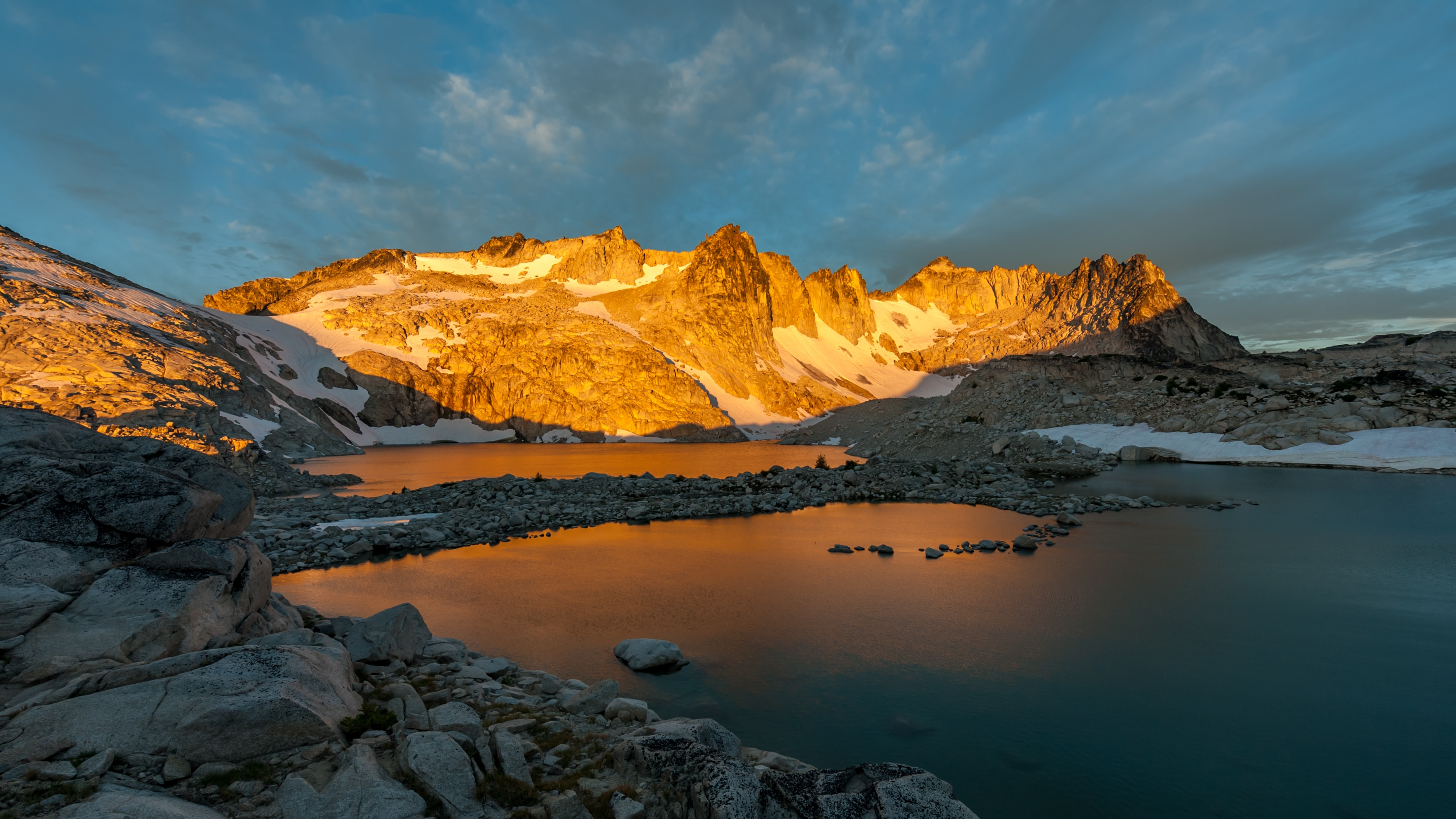 A snowcapped mountain range at Isolation Lake, with a sunset casting a bright light over the peaks