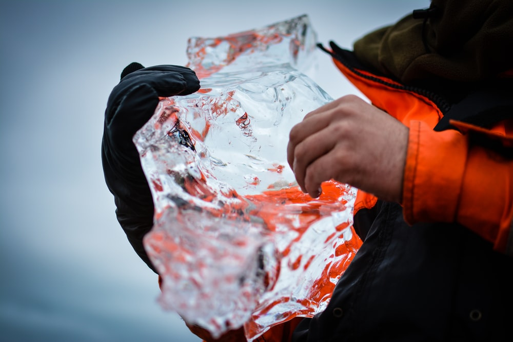 person holding clear crystal