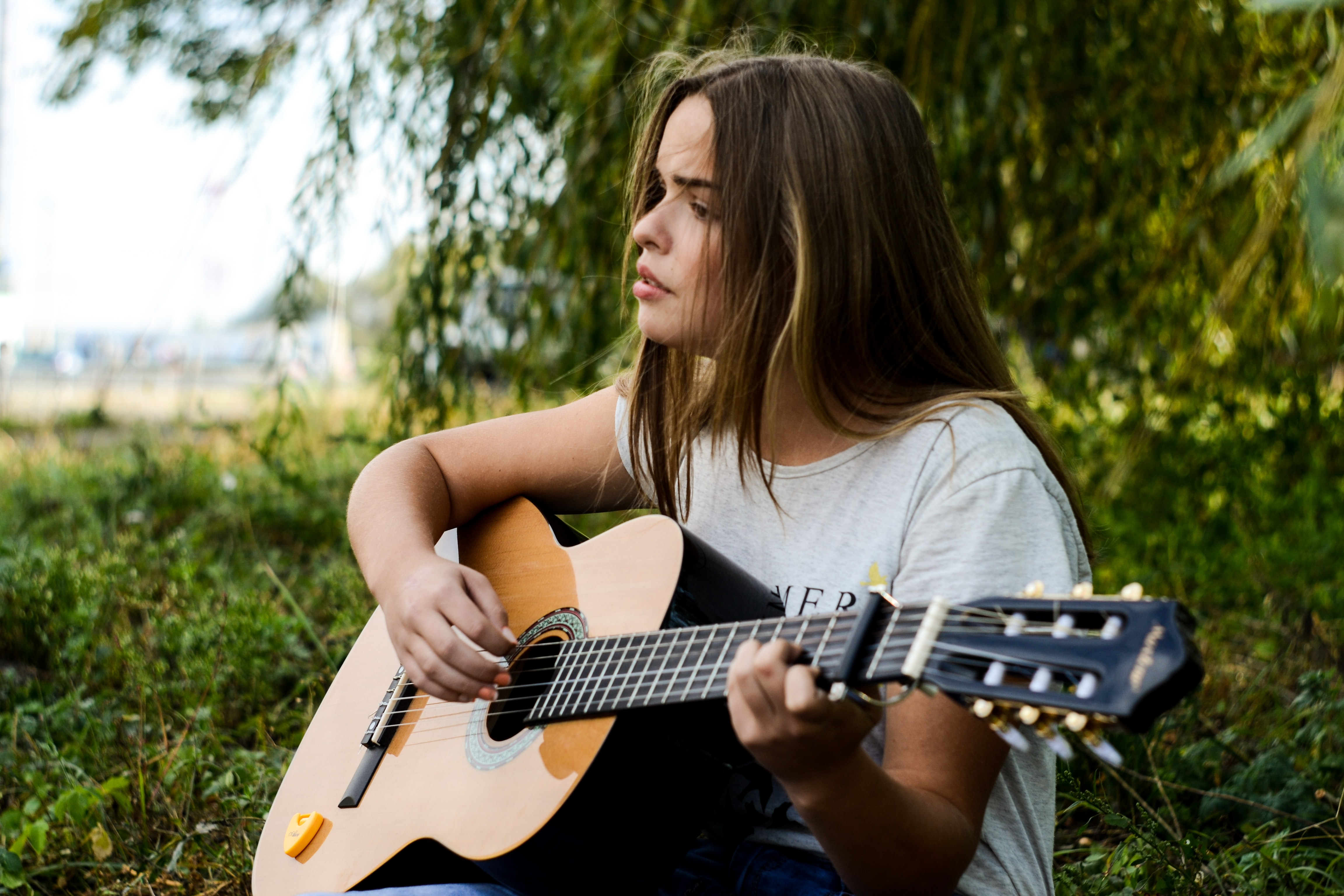 A young dark-haired woman playing acoustic guitar while sitting on grass